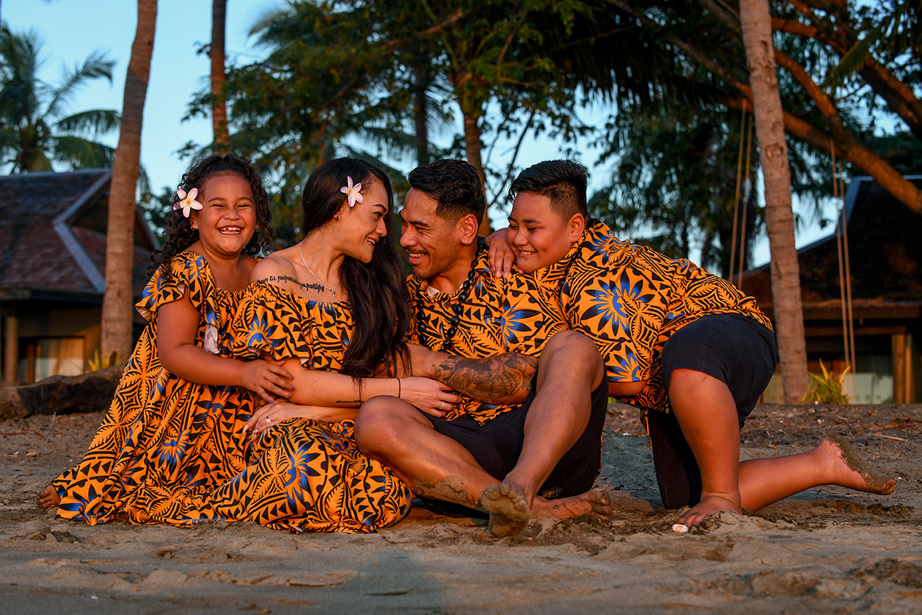 The family huddles on the beach with the sunset glowing off their skin at Double Tree Hilton Fiji