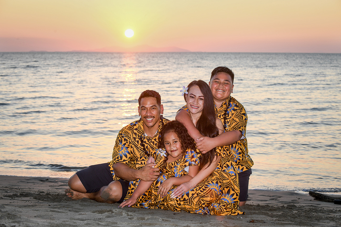 The family cuddles on the shore, behind, a golden Fiji sunset