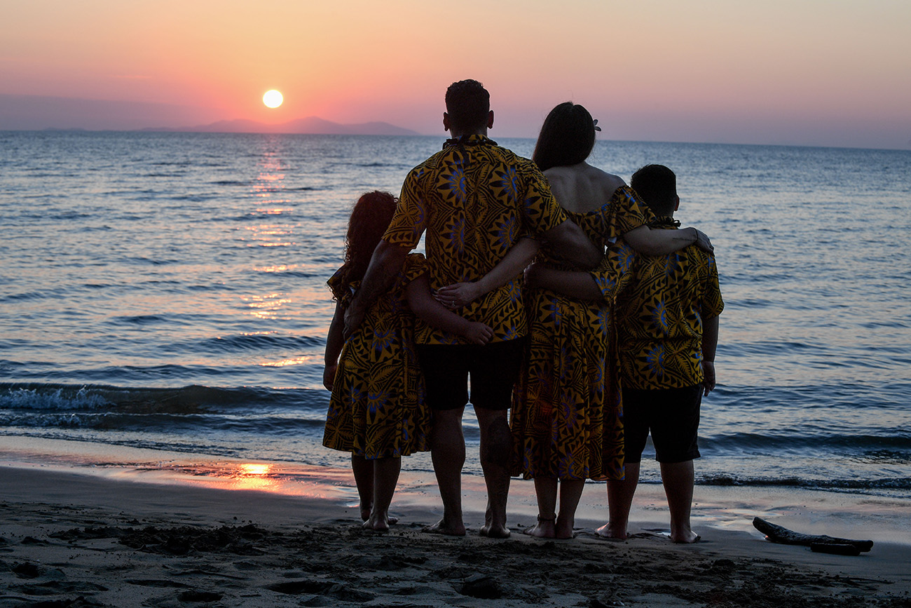 A silhouette befalls the family watching the stunning pink Fiji sunset
