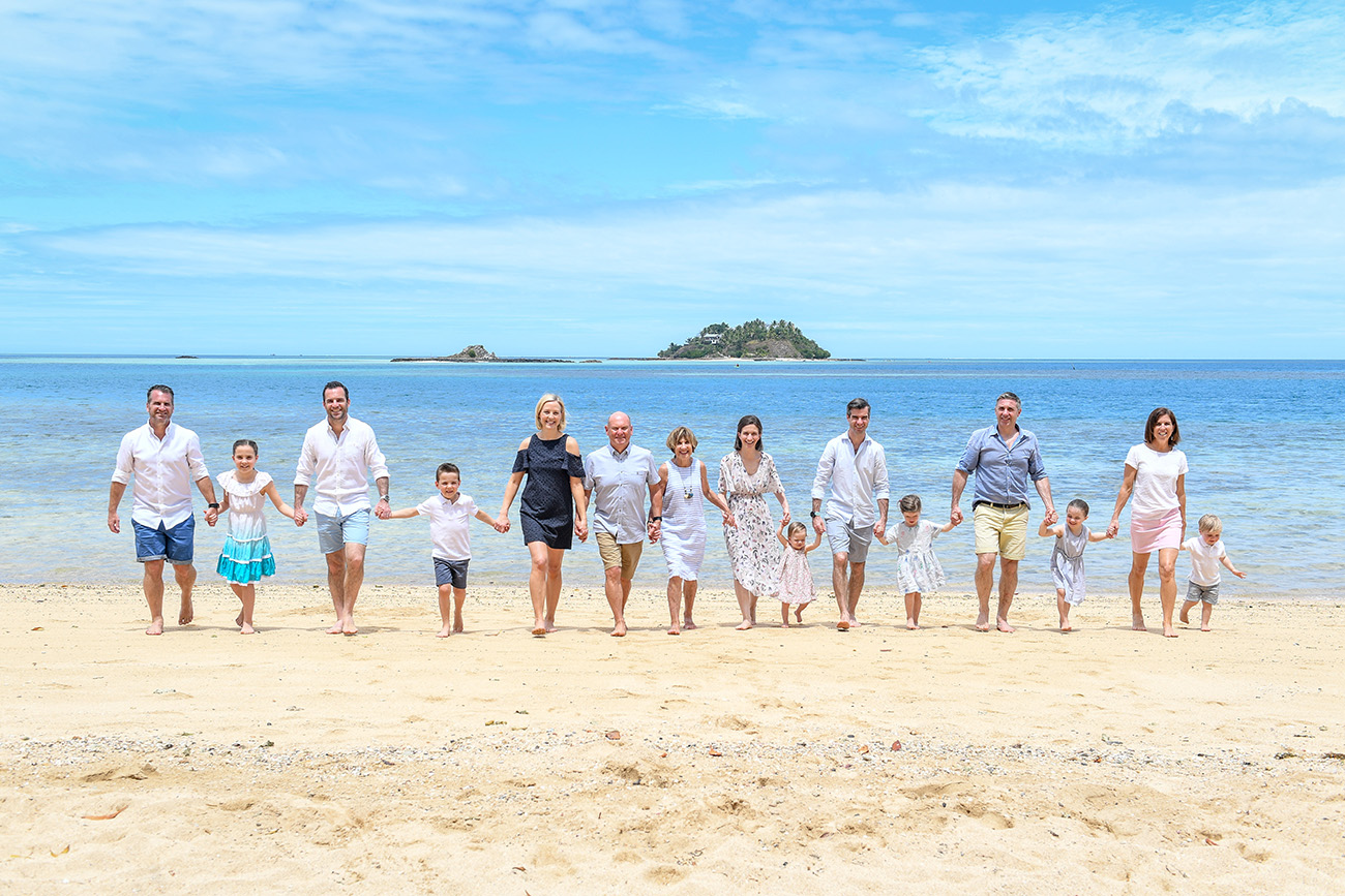 Three family generations hold hands as they walk together on the beach