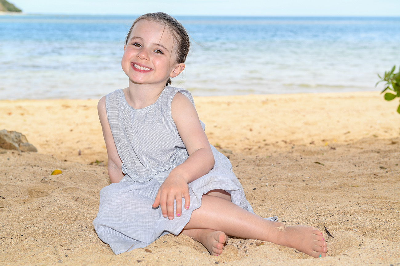 The cute brunette baby girl cracks a killer smile at the camera at Malolo Island beach