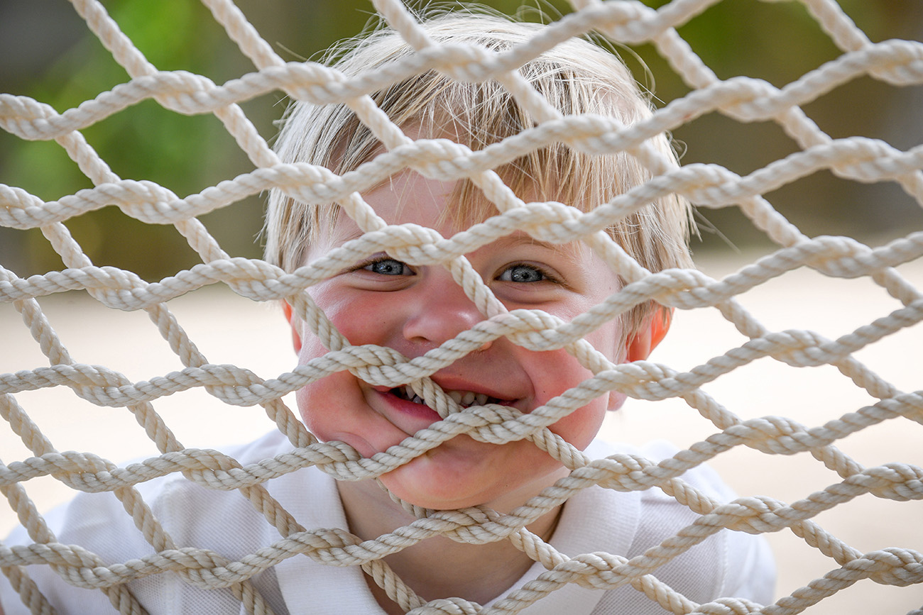 The cute baby grins at the camera through the hammock net