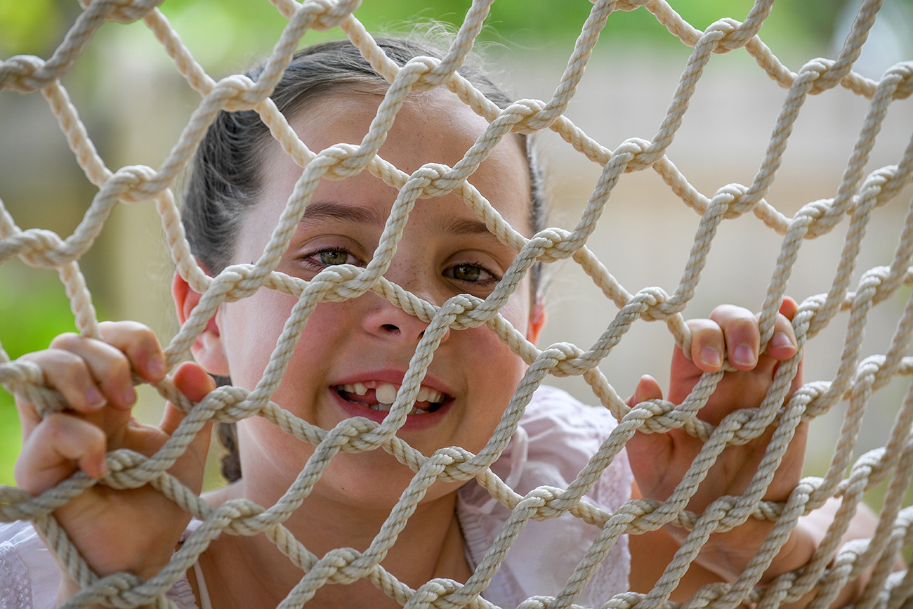 The cute little girl peers at the camera through the hammock net