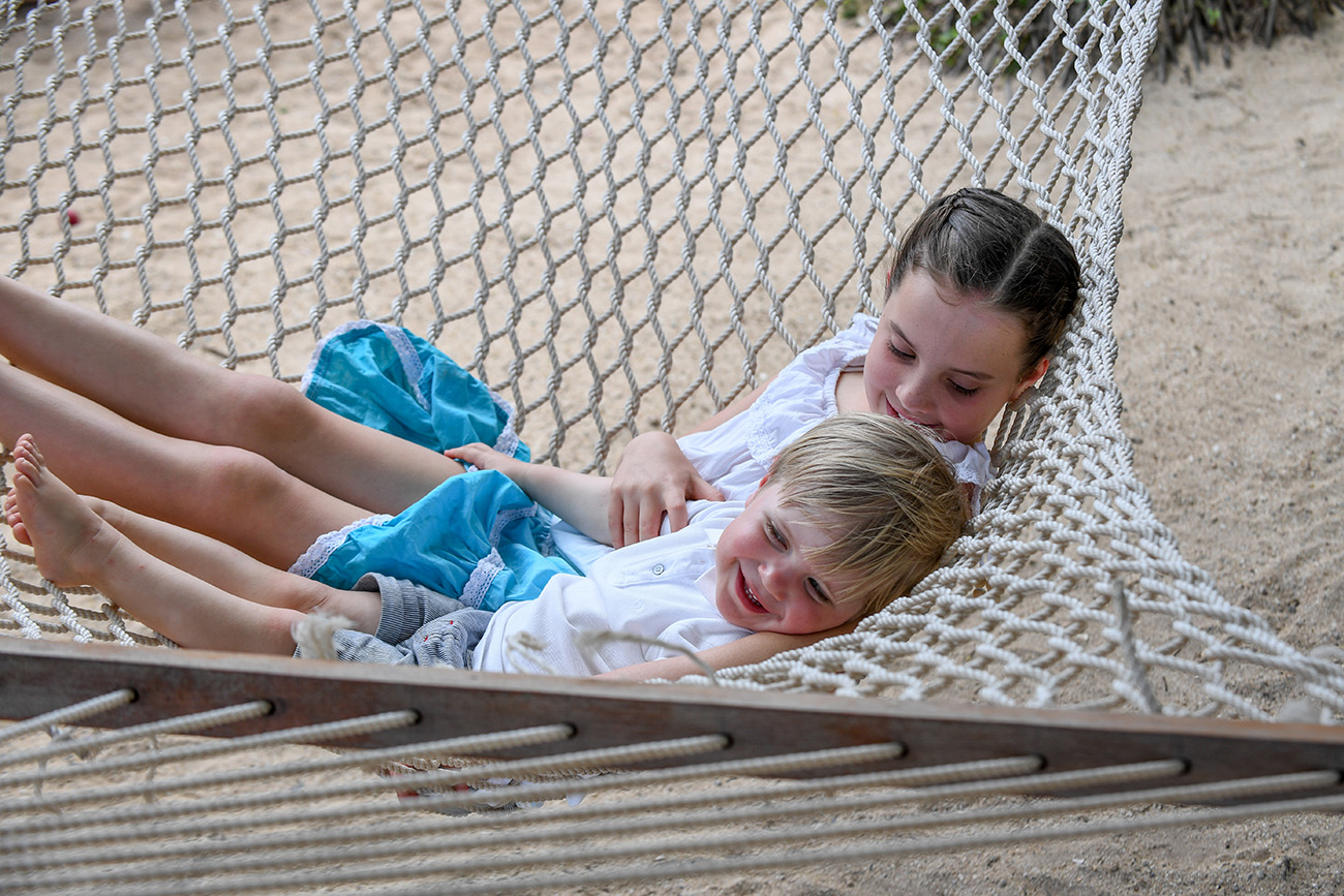 Brother and sister swing on hammock at Malolo Island Resort