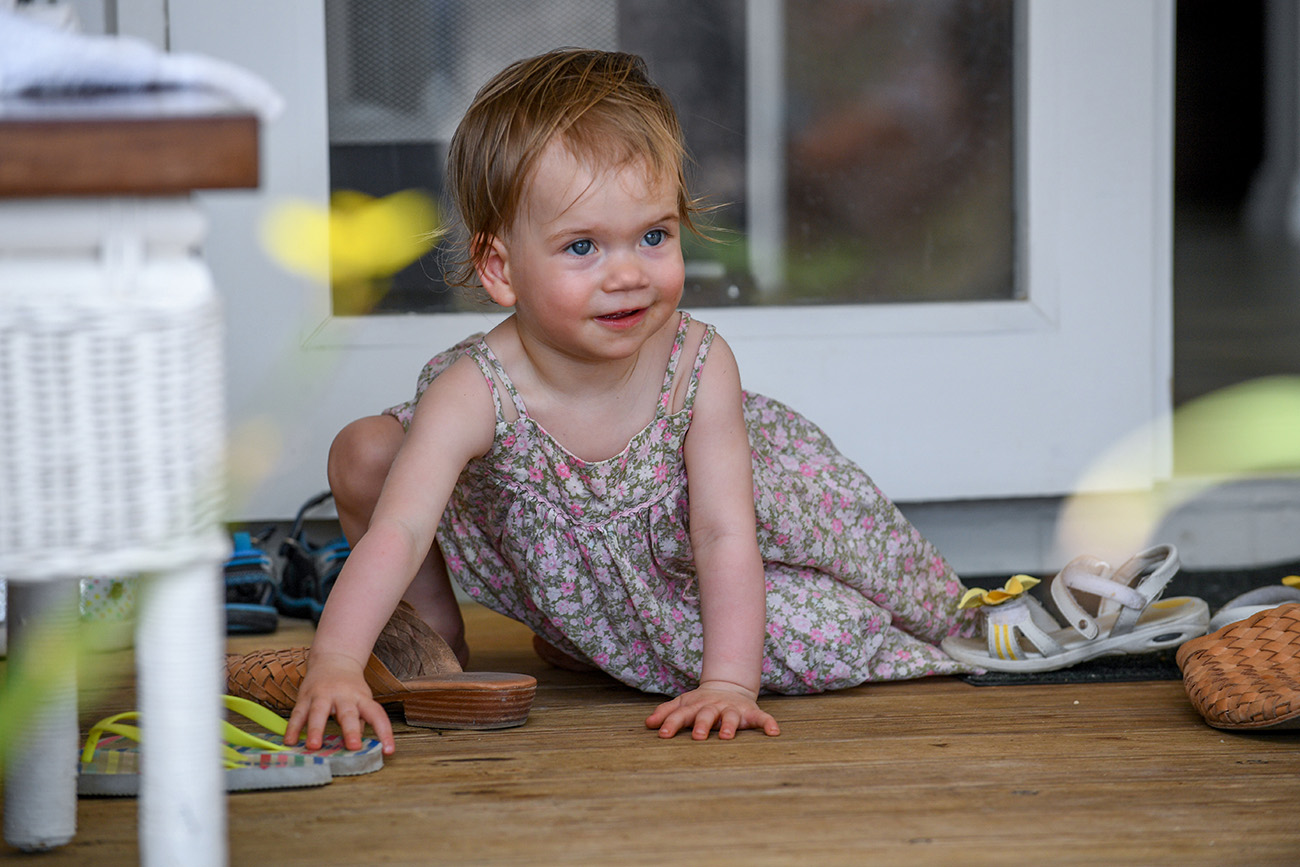 The cute ginger haired baby plays with sandals