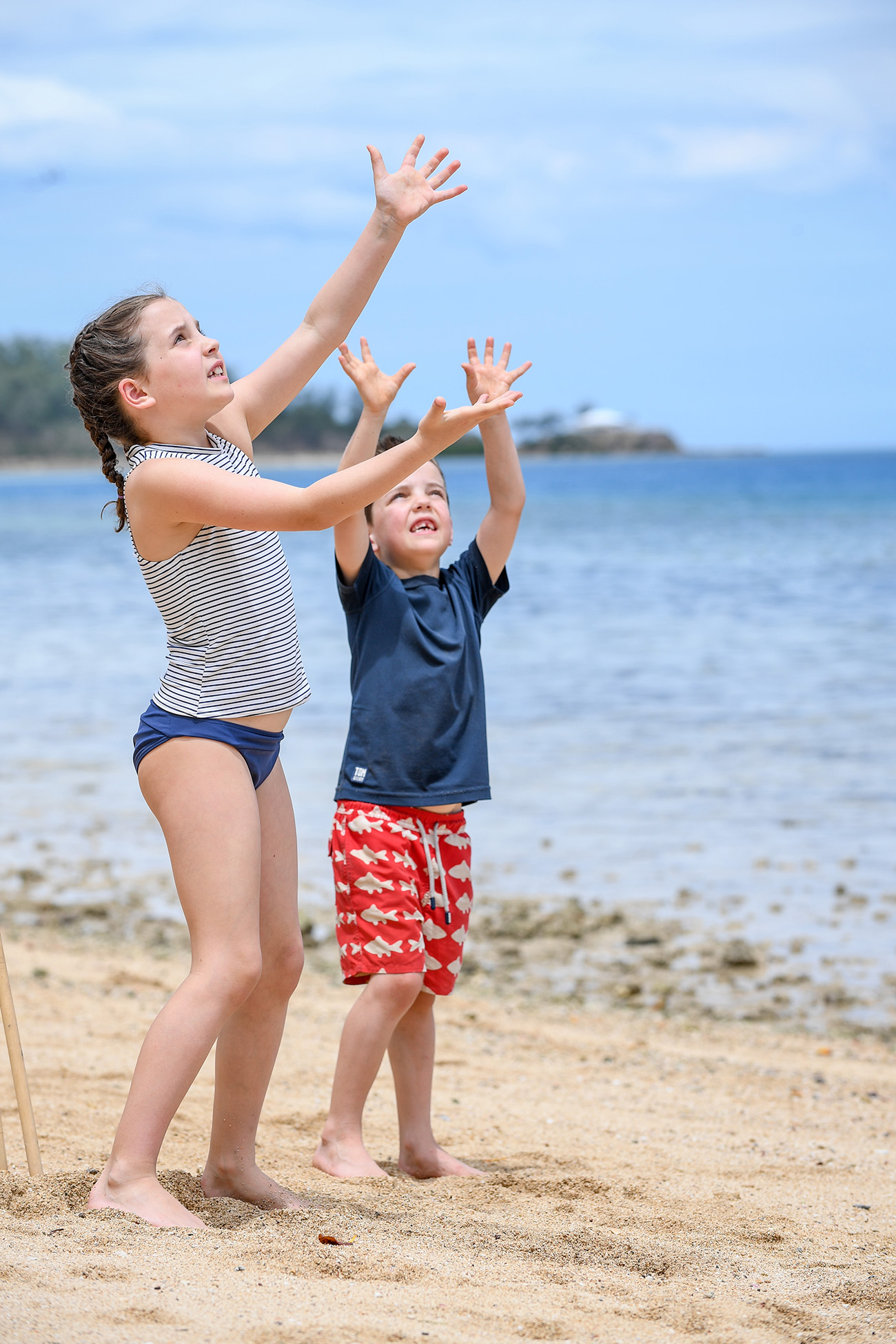 The cute babies reach for the cricket ball in the air while playing beach cricket