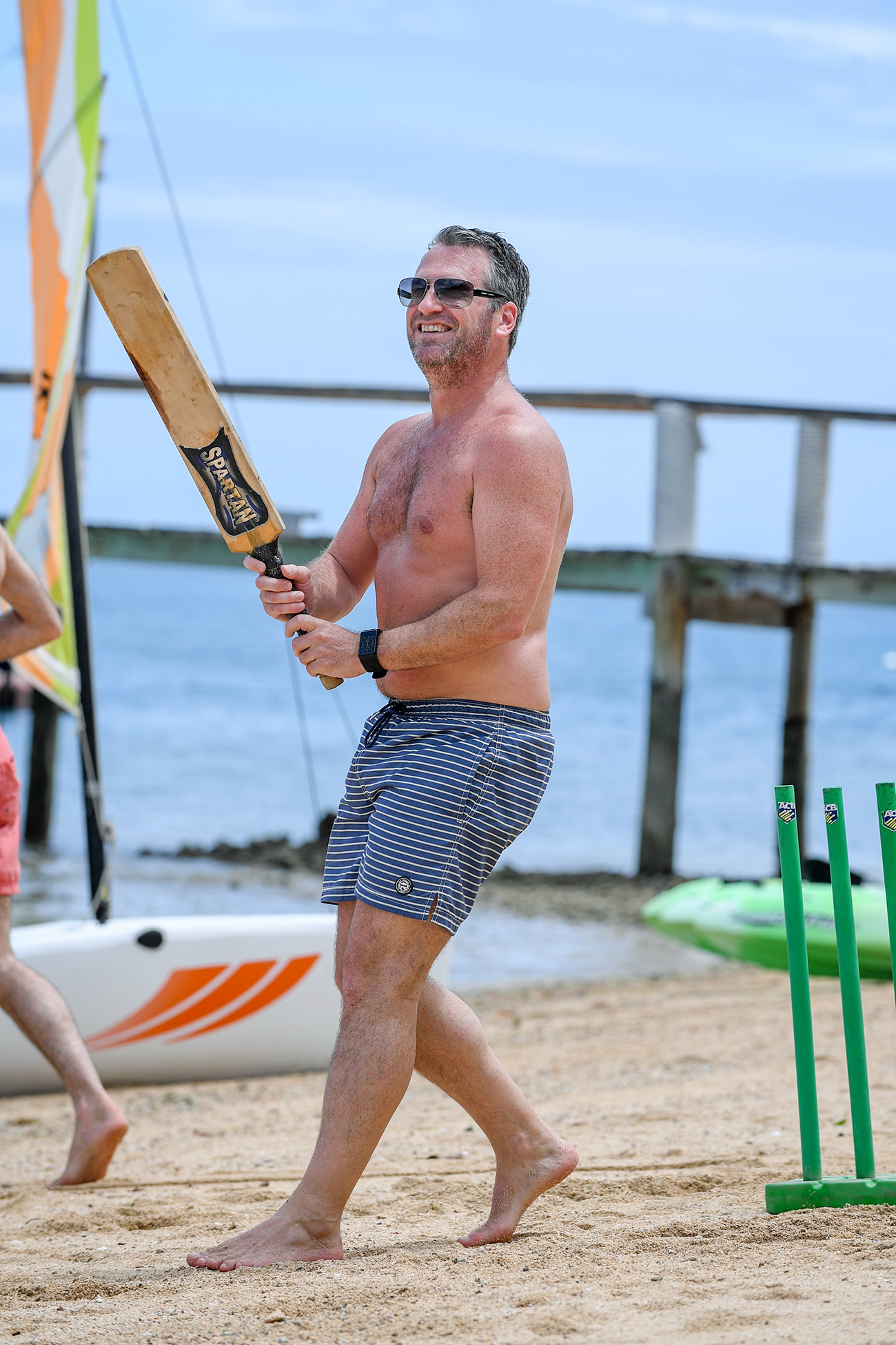 A dad watches the ball after batting while playing beach cricket
