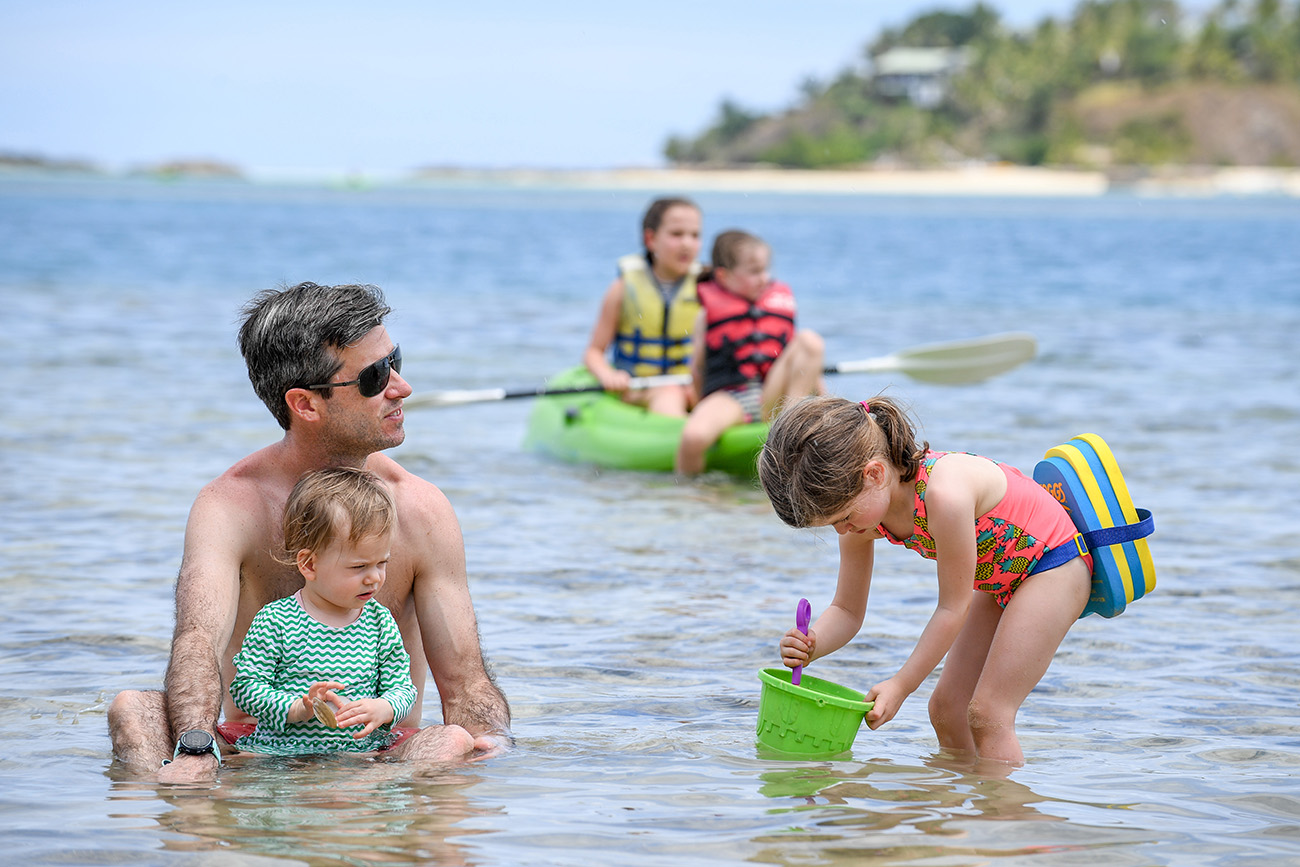 Father watches as his daughter gathers water for sandcastles