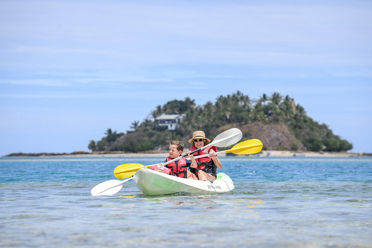 Mother and daughter paddle on the shallow waters at Malolo Island