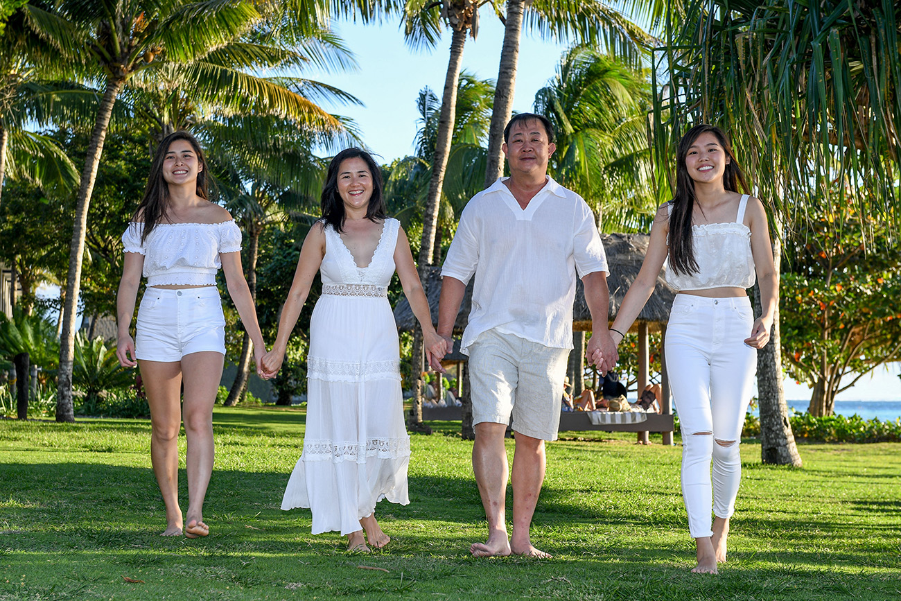 Asian family holds hands while walking on the manicured green grass at Natadola Fiji