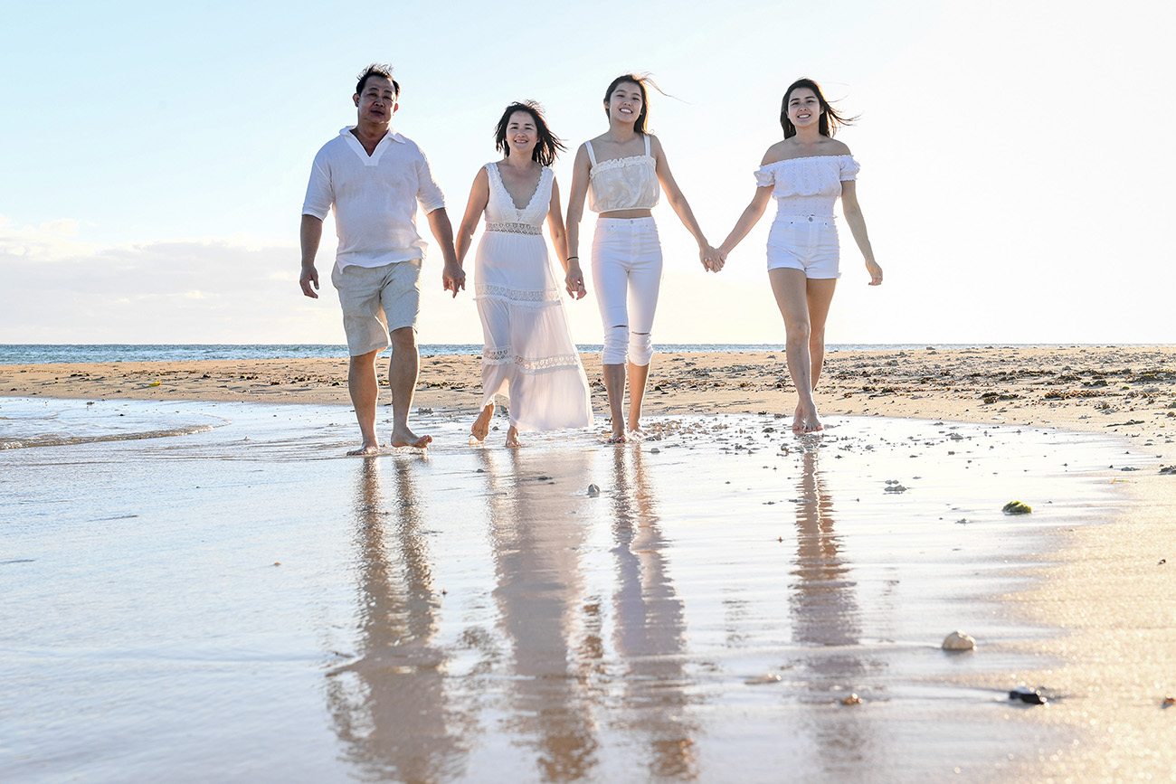 Adults hold hands and stroll on the sea