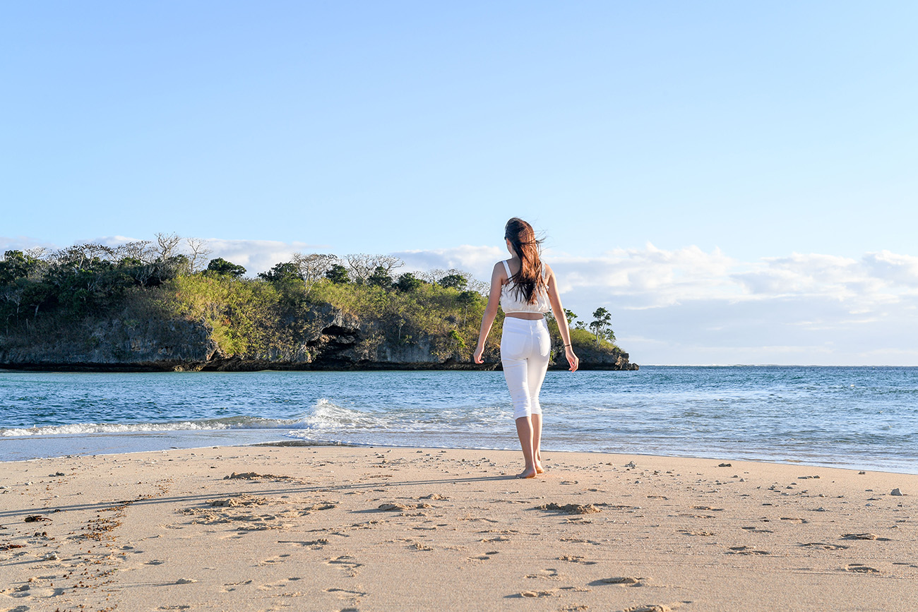 A woman takes a lonely beach stroll