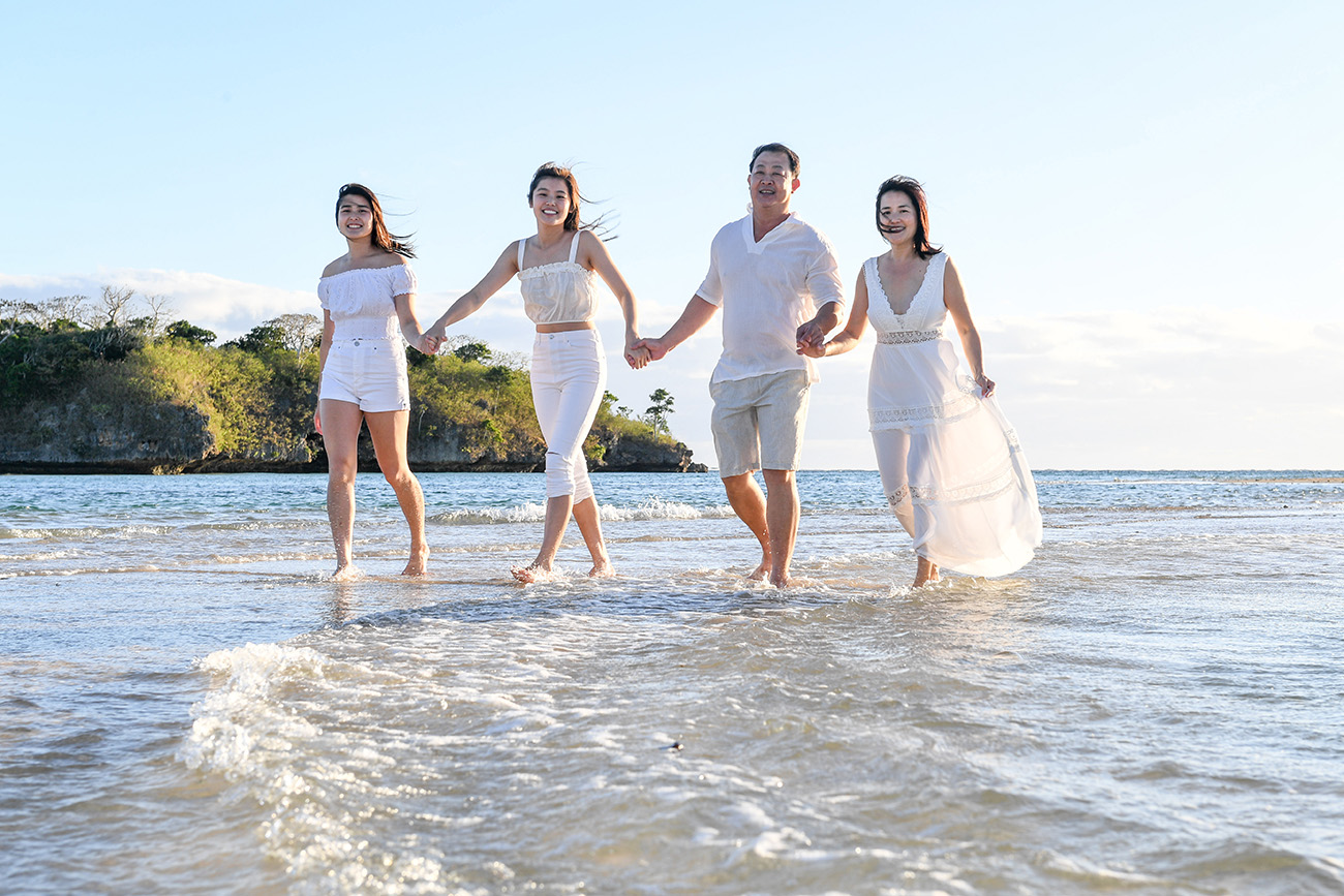 A family hold hands as they stroll in the Pacific ocean