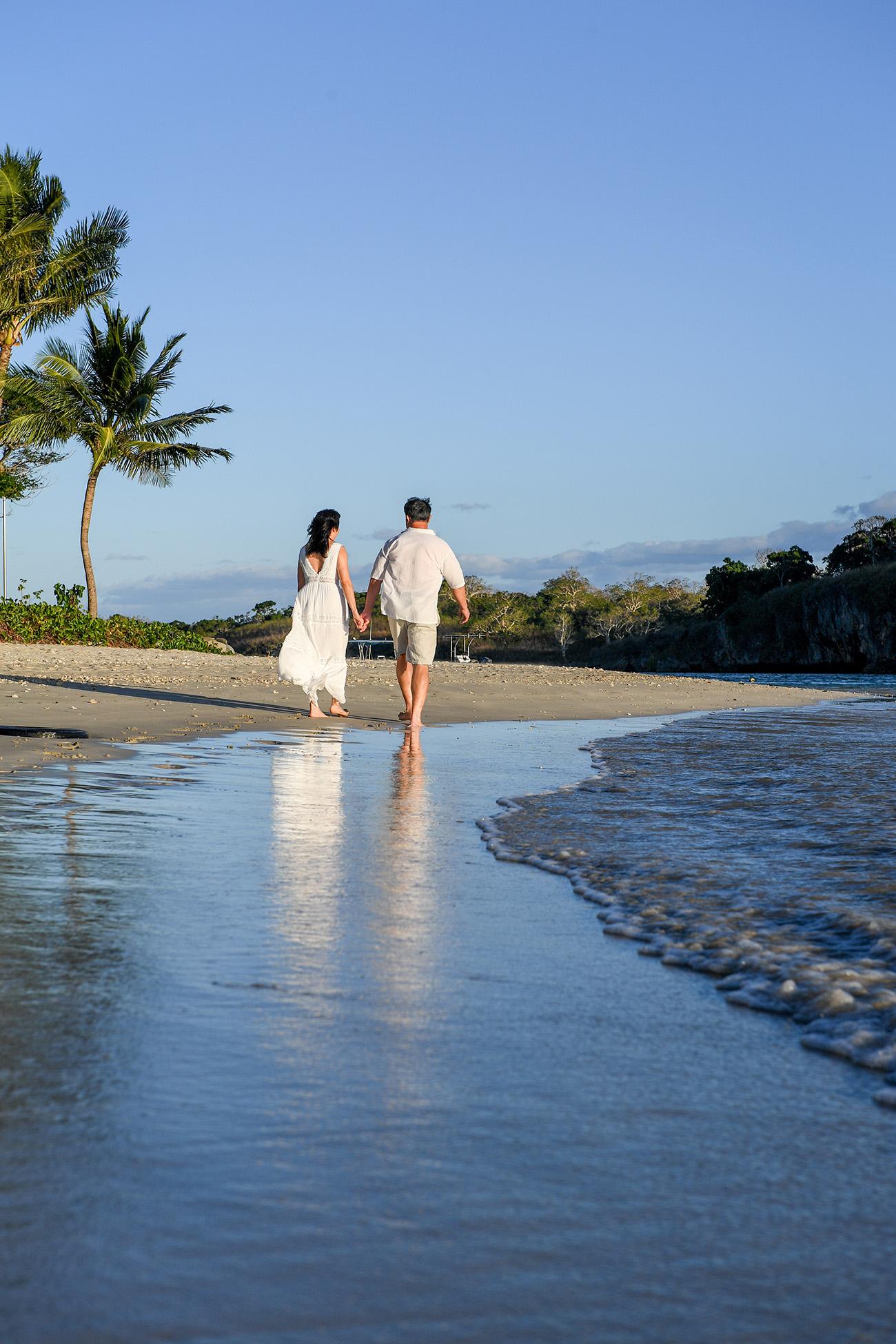 An asian couple strolls on the beach at Natadola Fiji
