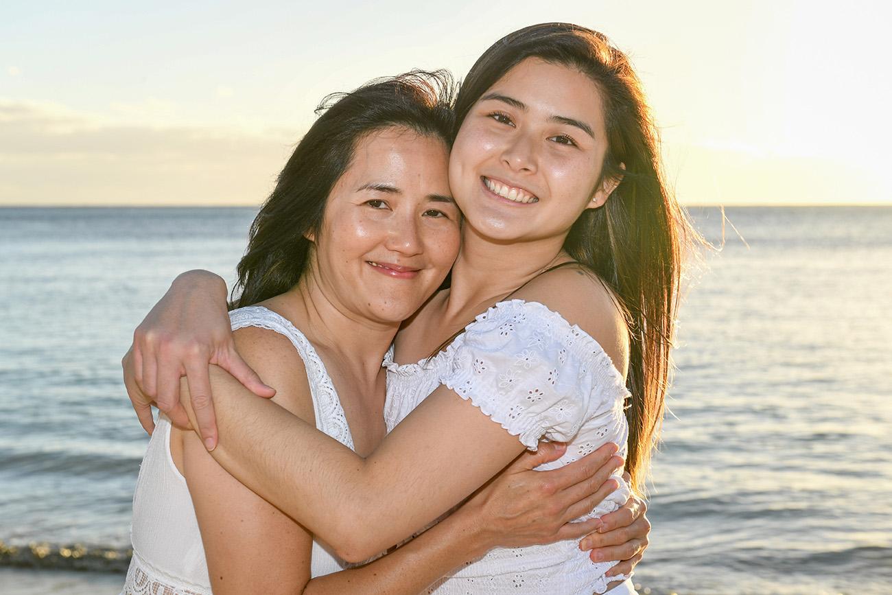 Mother hugs daughter against Fiji sunset