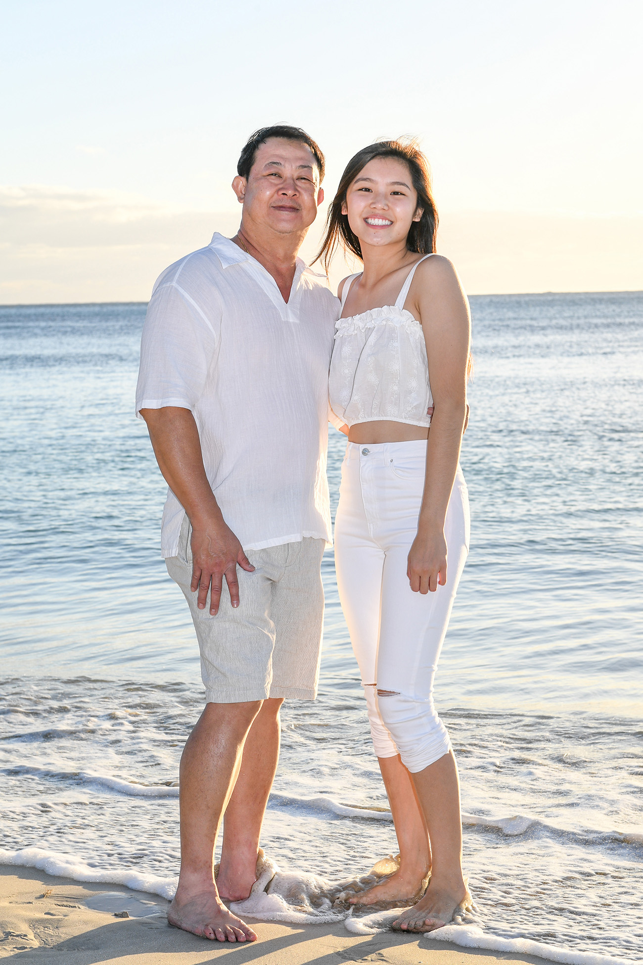 Asian father and daughter pose against the Fiji sea at sunset