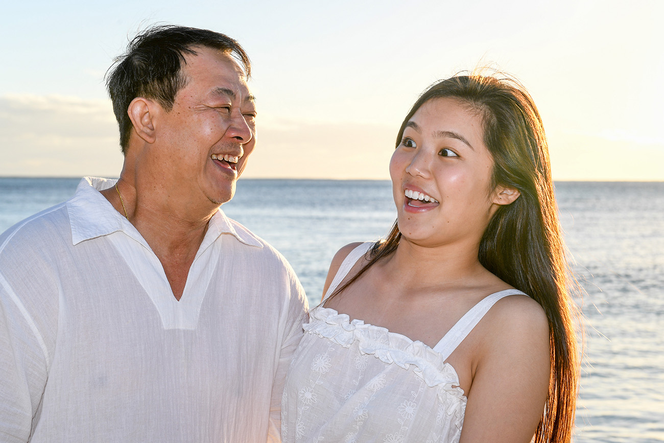 Asian father laughs with his daughter in the Fiji sunset