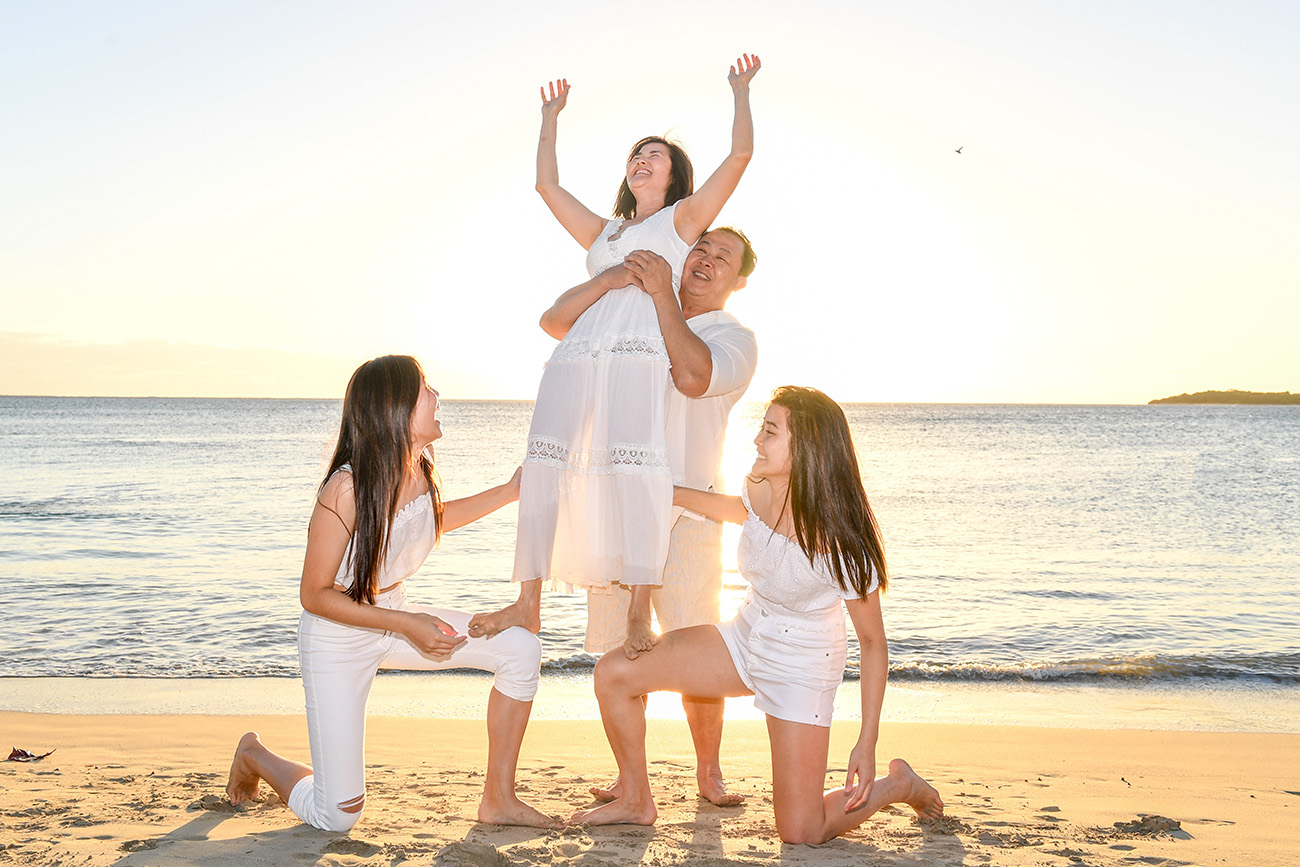 A family lifts their mother in the air at the Fiji sunset