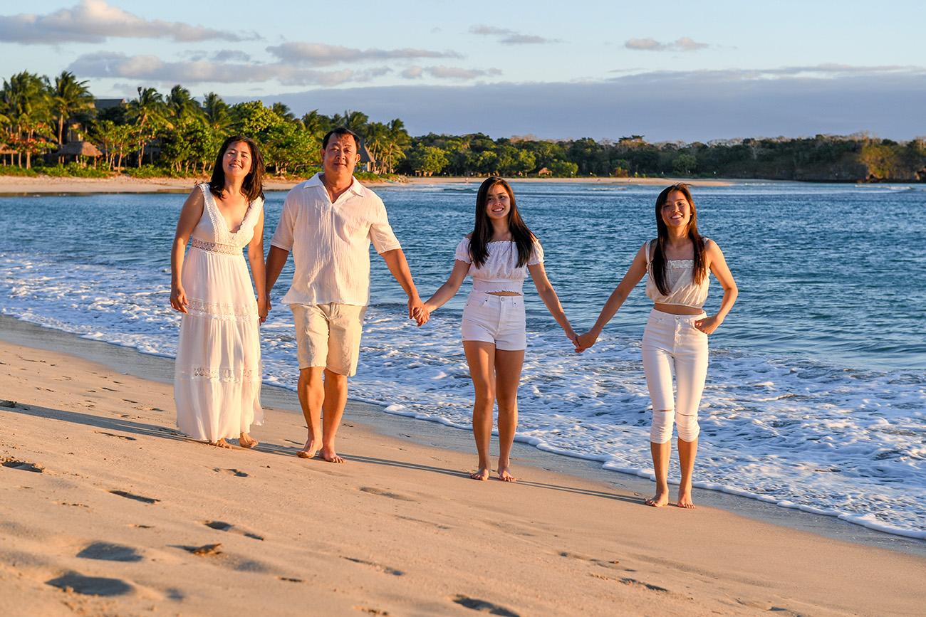 Asian family strolls on the beach