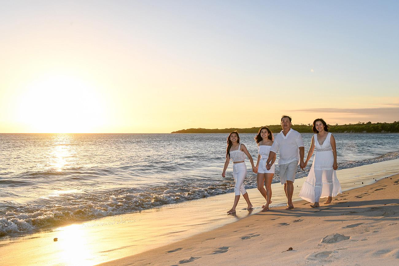 The family strolls beside the golden Fiji sunset