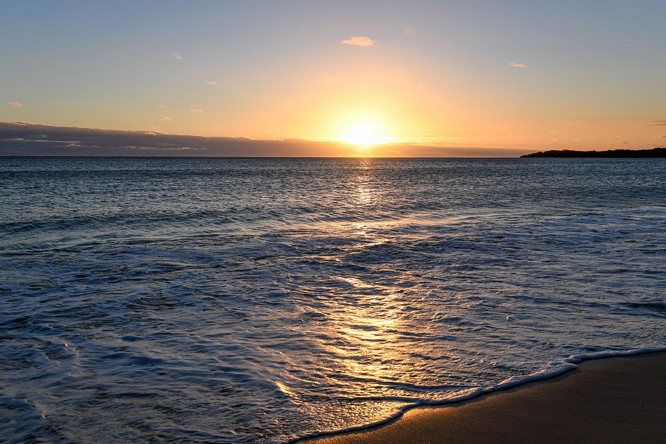 The golden sun sets behind the Pacific ocean in Denarau Fiji