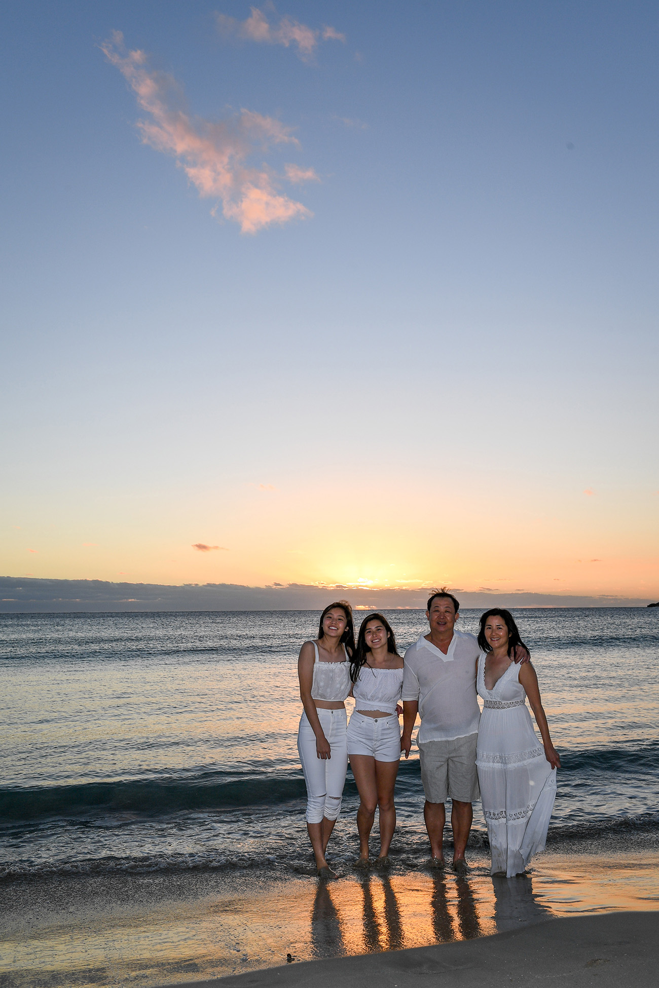 The family cuddles against the setting Fiji sun
