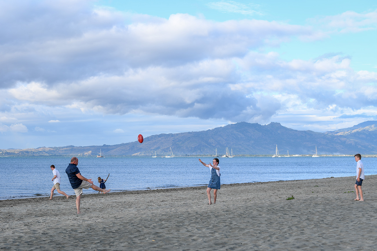 The family plays beach rugby against baby blue sky