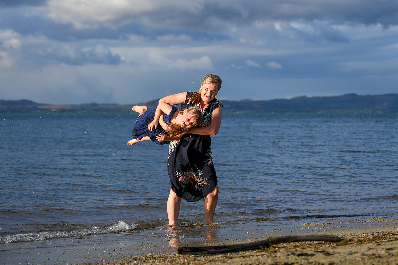A mother tackles her daughter on the beach at Denarau Fiji