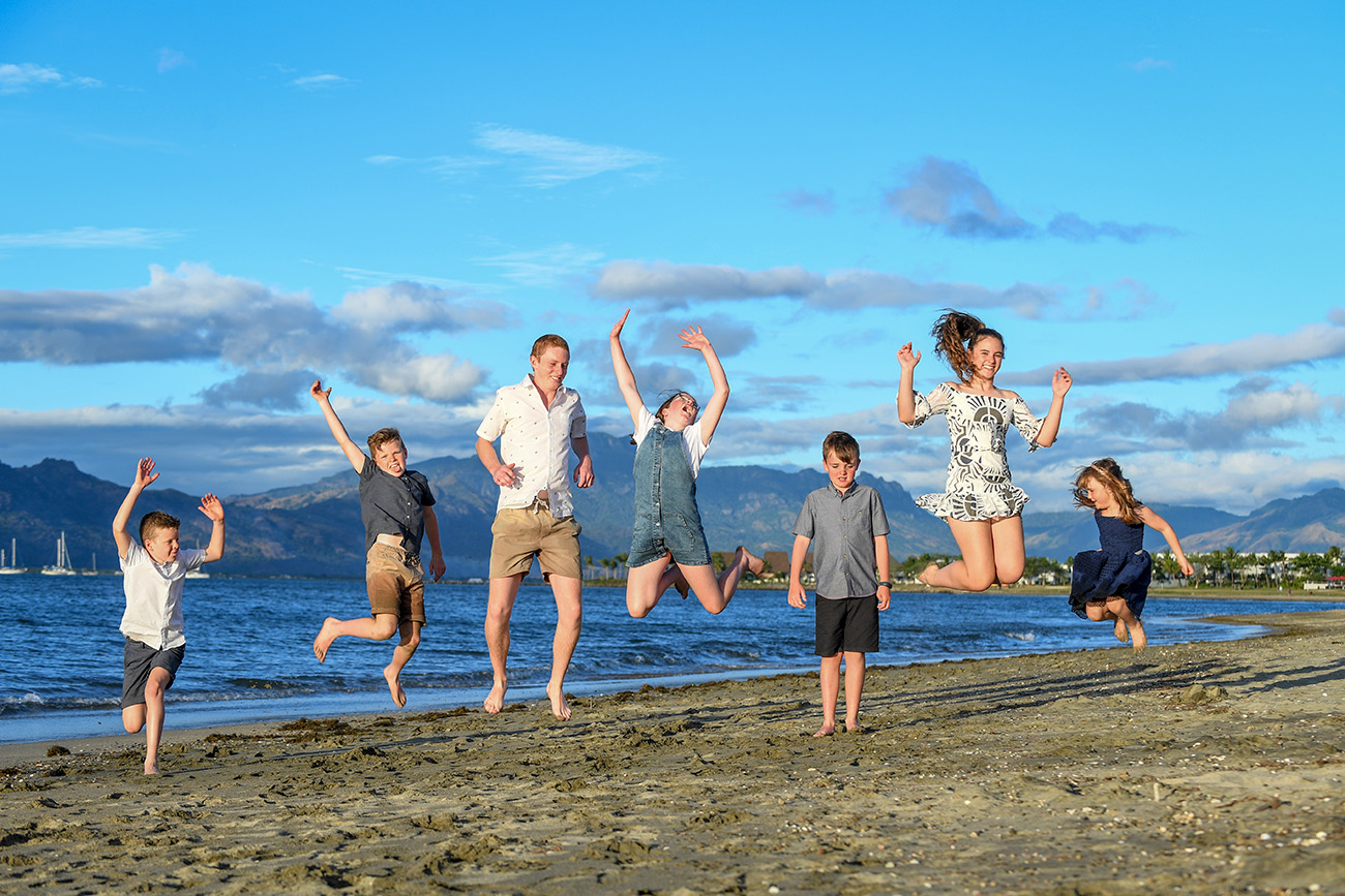 A group of kids leap in the air on the beach