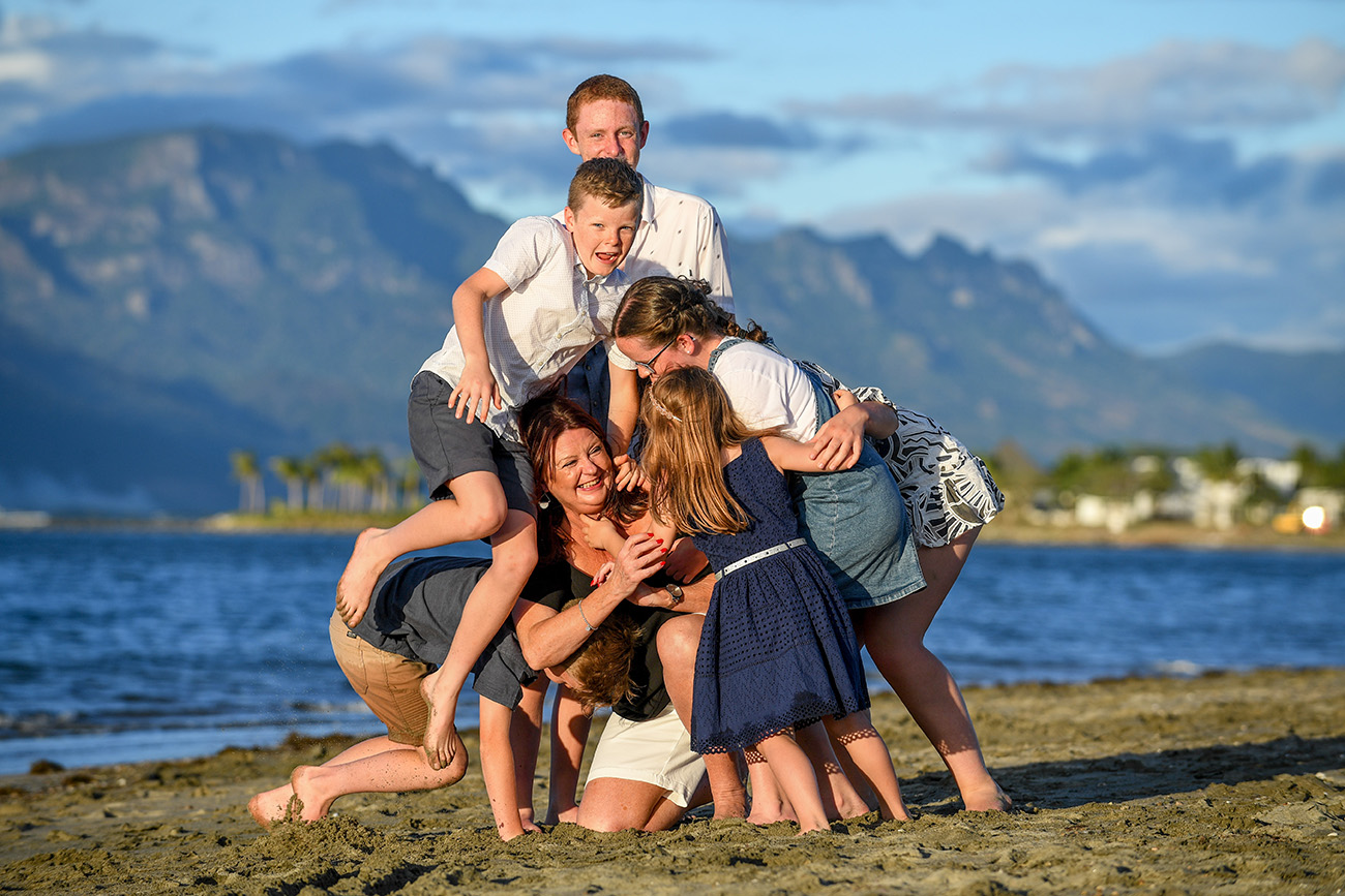 Kids climb over their mother at the beach