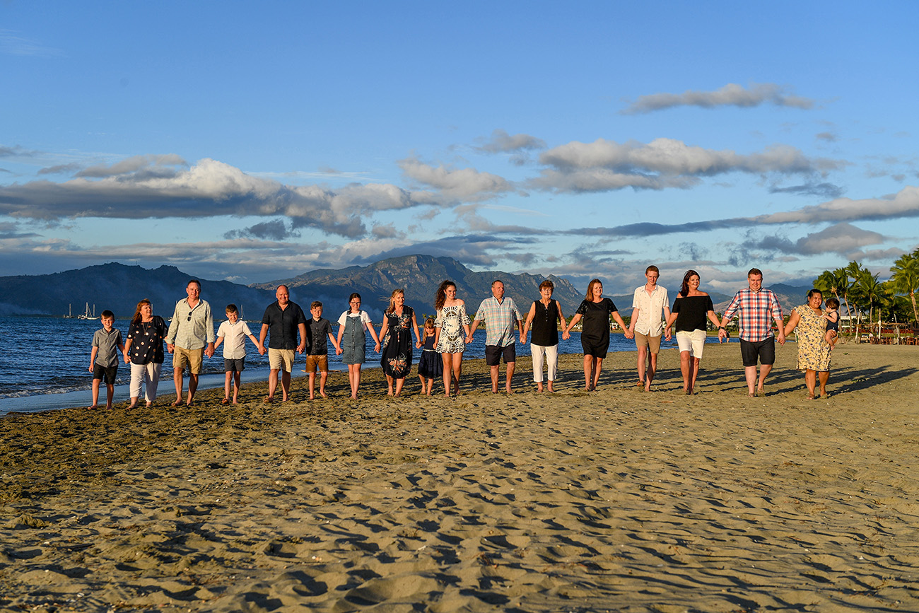 Extended caucasian family holds hands as they walk together on the beach