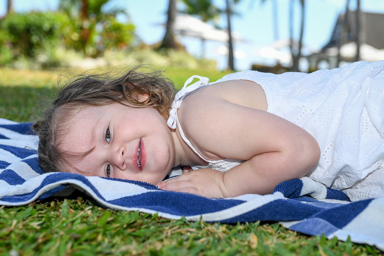 Cute baby girl lies down on a blue towel on green grass