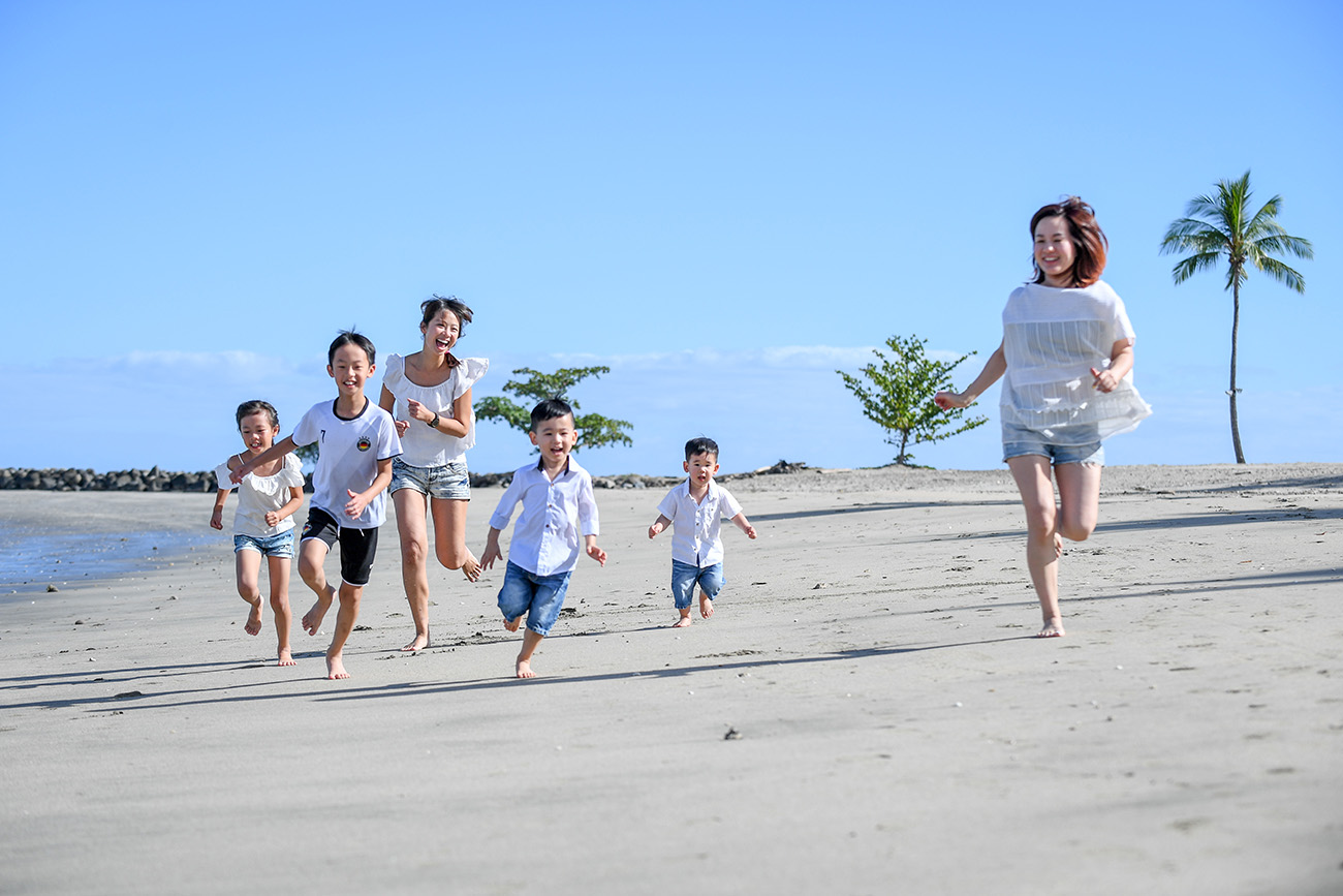 Two families run on the beach against baby blue sky