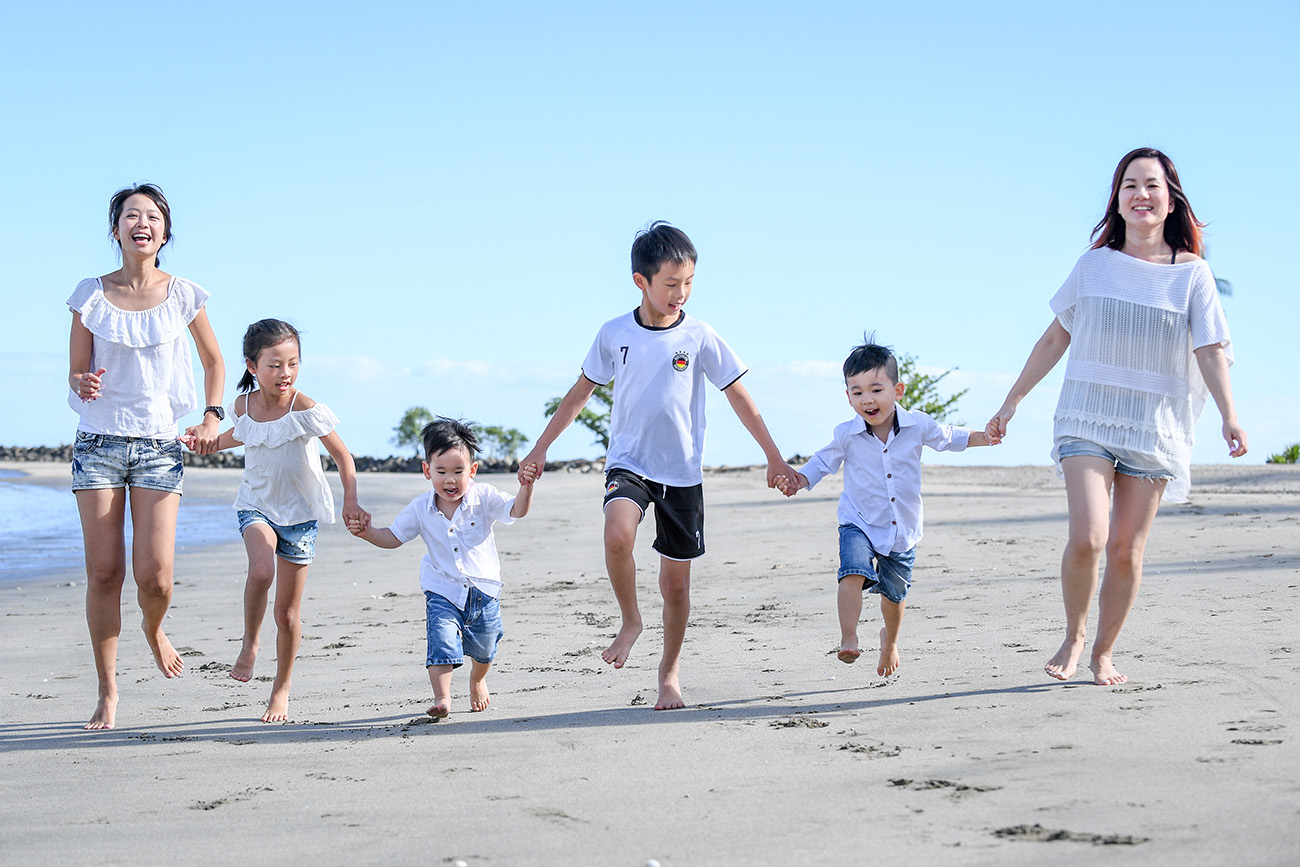 Cute asian family hold hands and run on the beach at Natadola Fiji