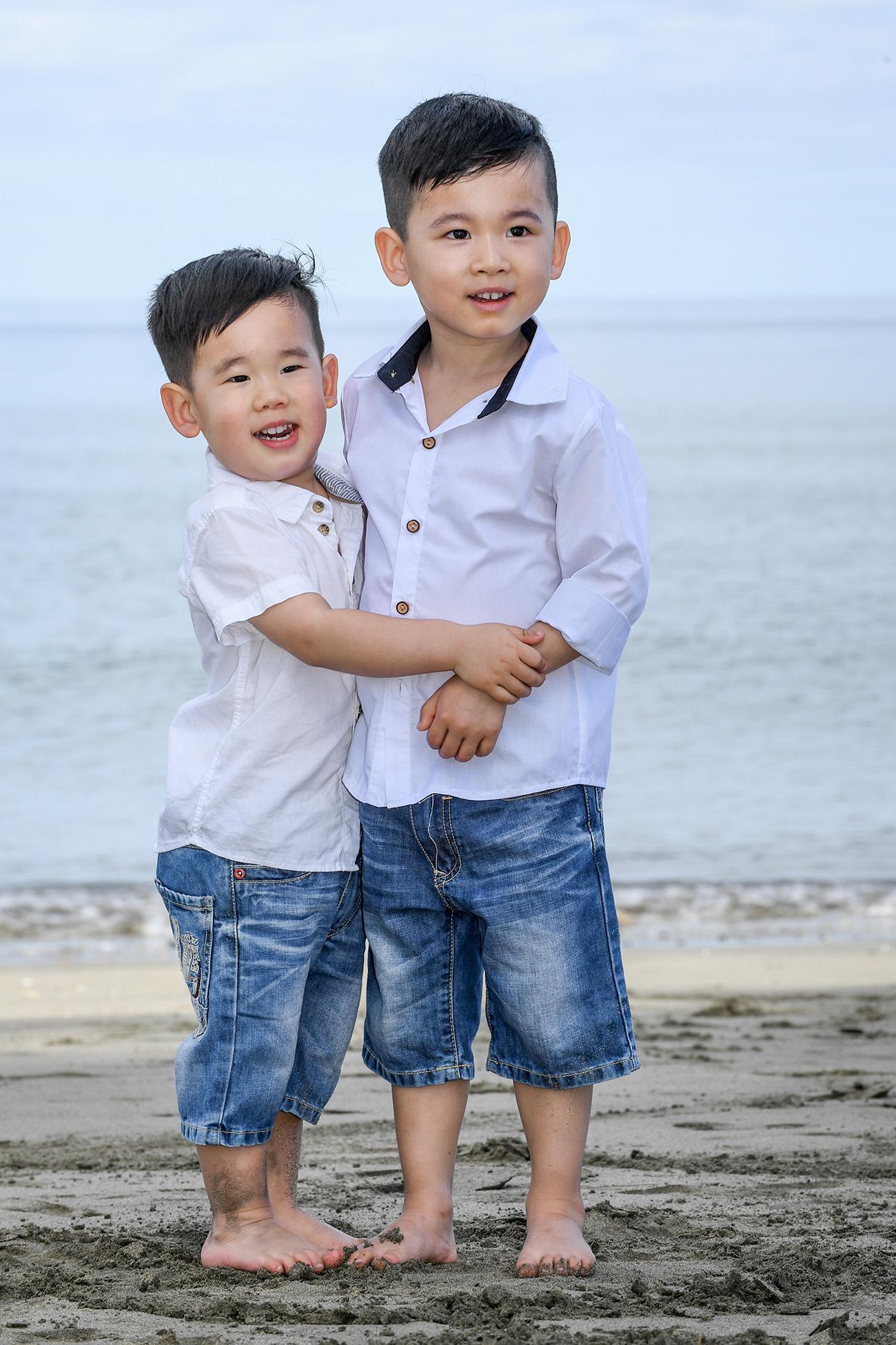 Two asian baby brothers hug while at the beach at Natadola Fiji