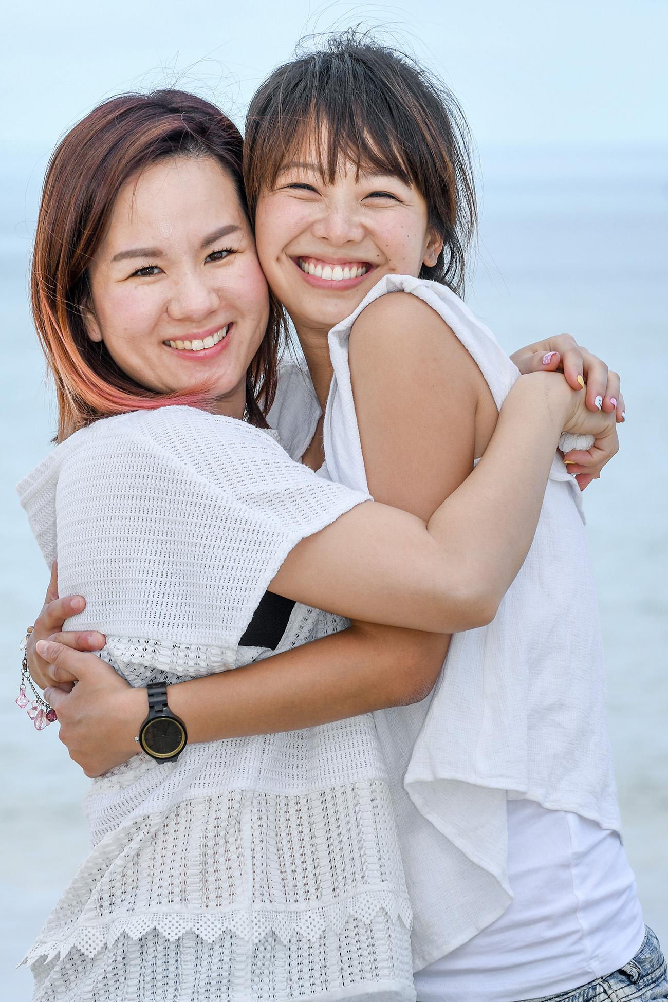 Asian sisters hug while at the beach at Natadola Fiji