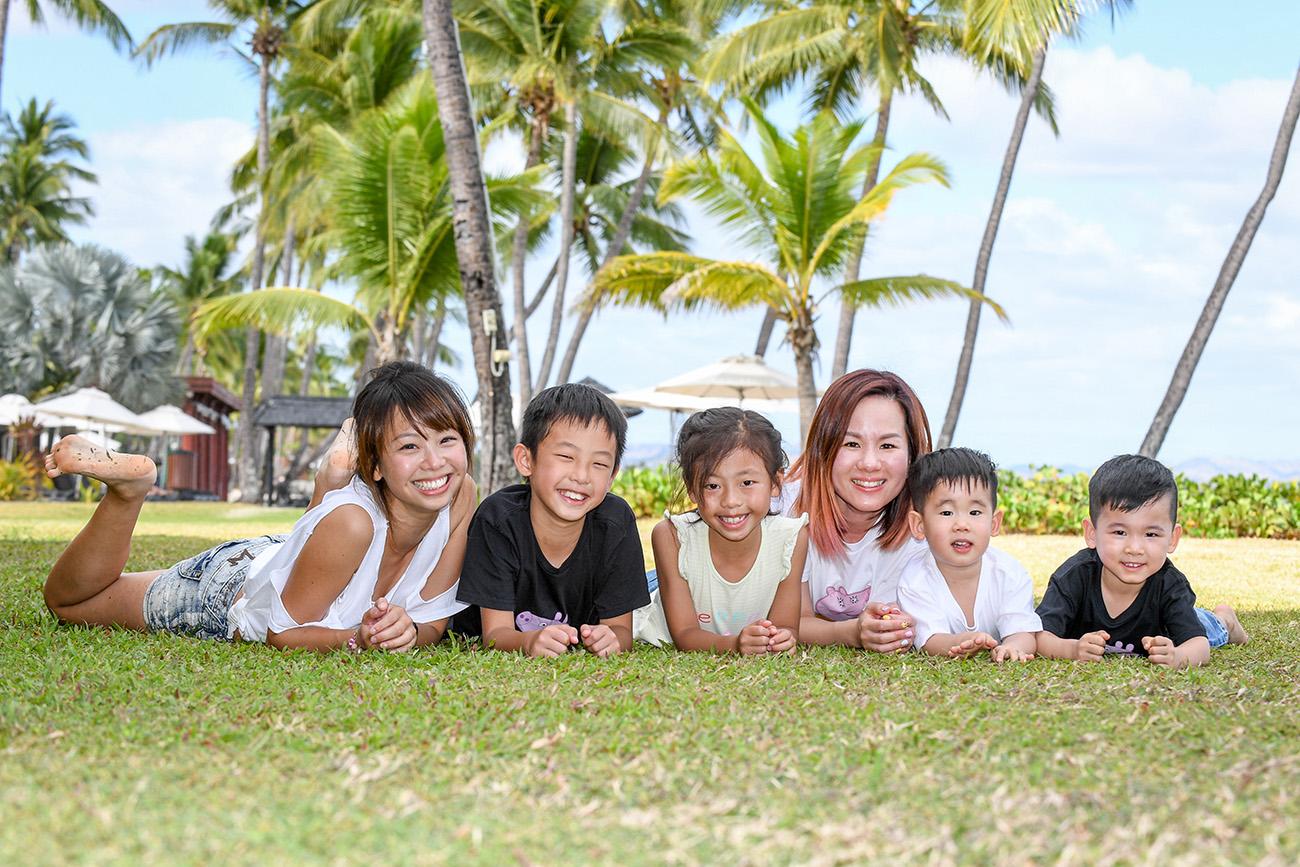 Asian siblings pose on the manicured grass at Natadola Fiji