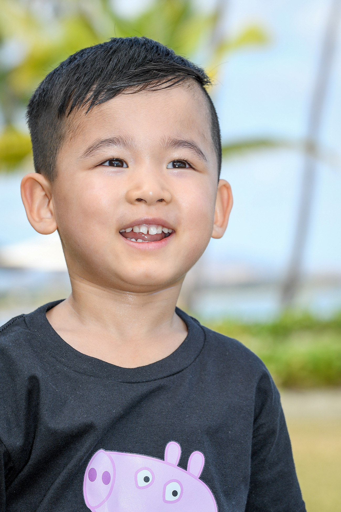 Cute asian boy on the beach against baby blue skies