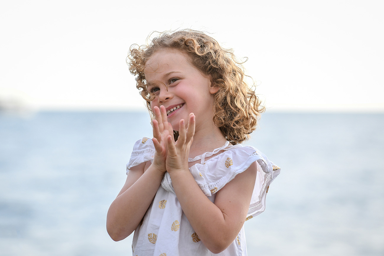 Cute wavy haired girl claps while on the beach