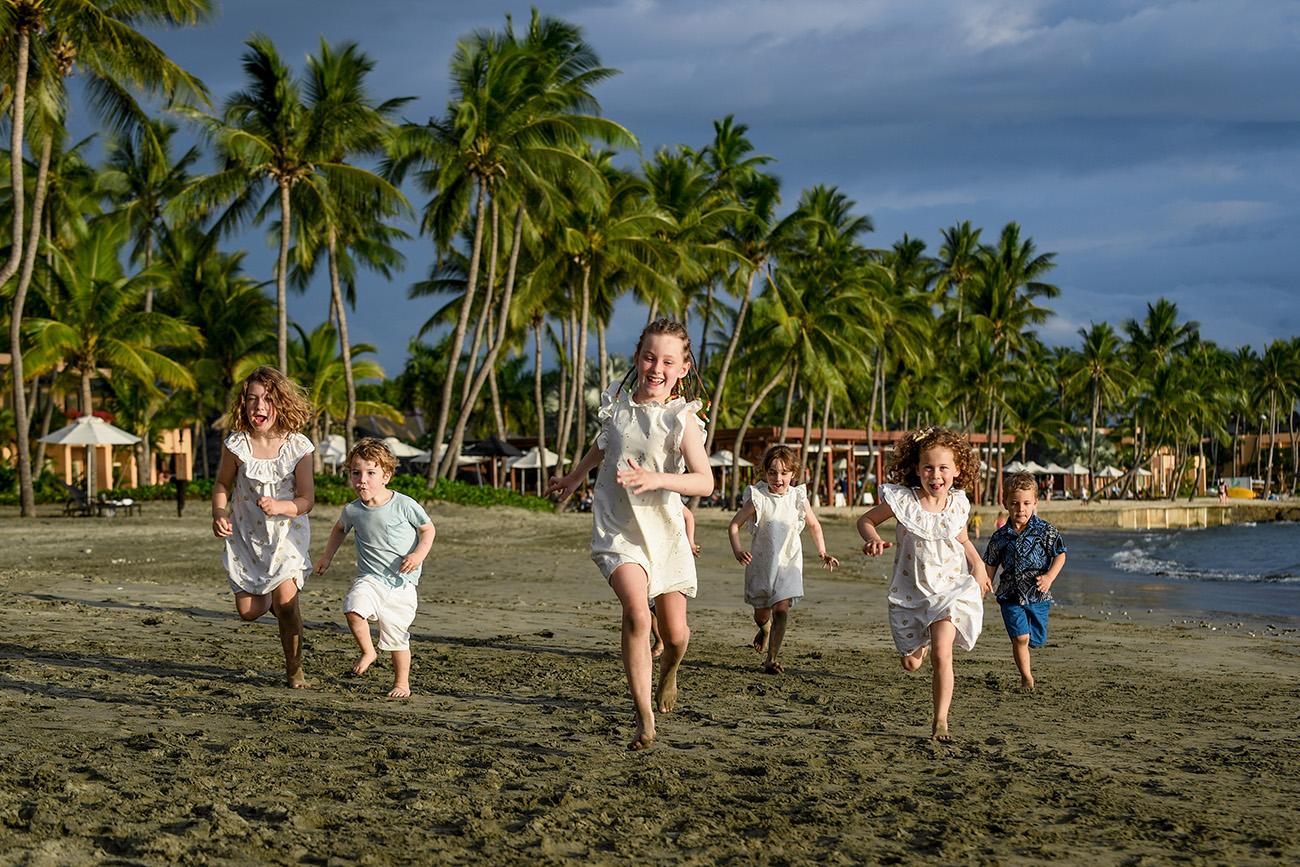 Cousins in white run on the beach against palm trees