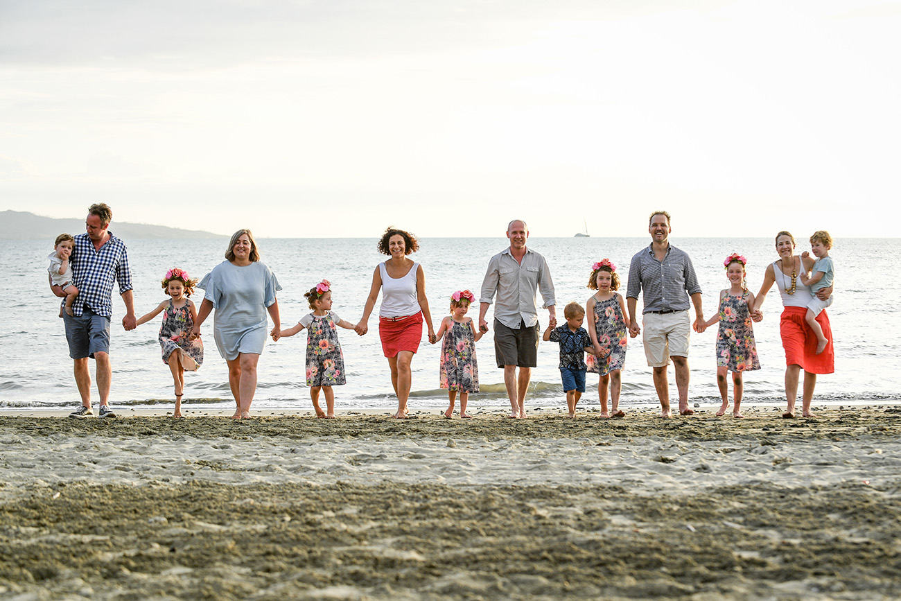 An extended family in matching outfits walks on the beach