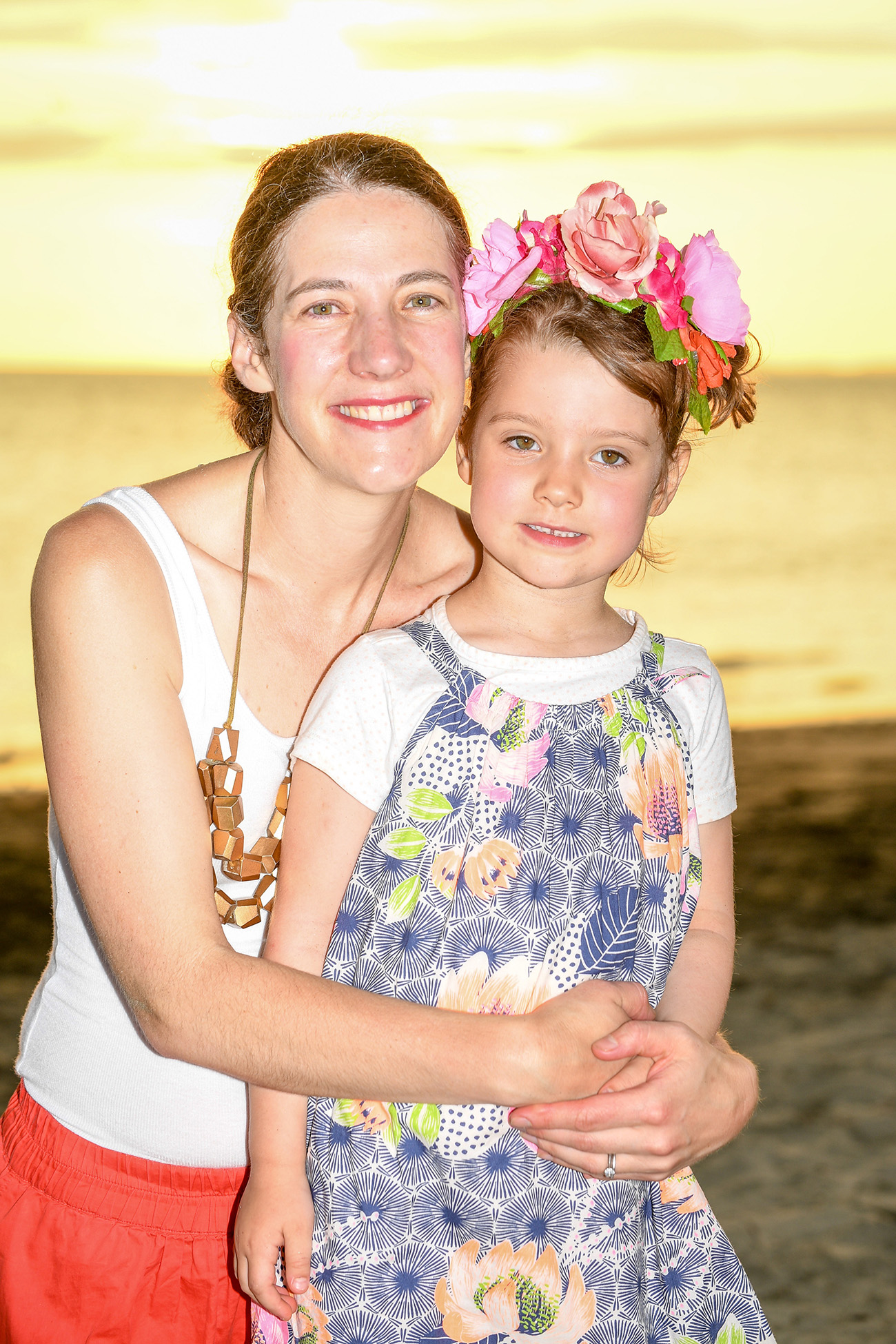 A mother hugs her daughter wearing a flower crown