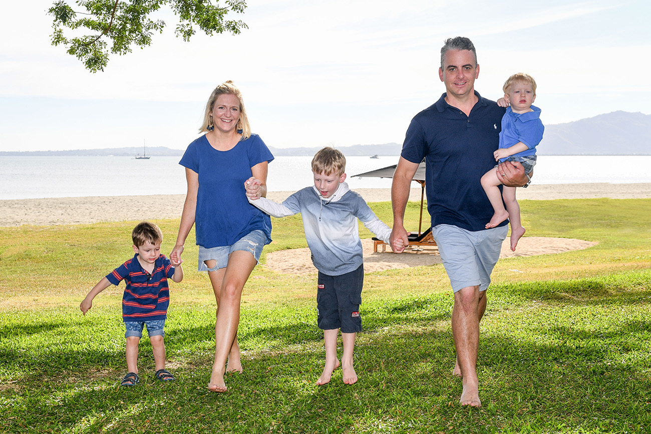 A family in blue walks on manicured lawn of Natadola Fiji