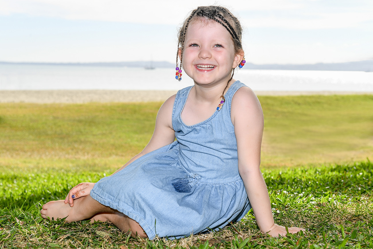 A cute little braided girl smiles at the camera seated on manicured grass