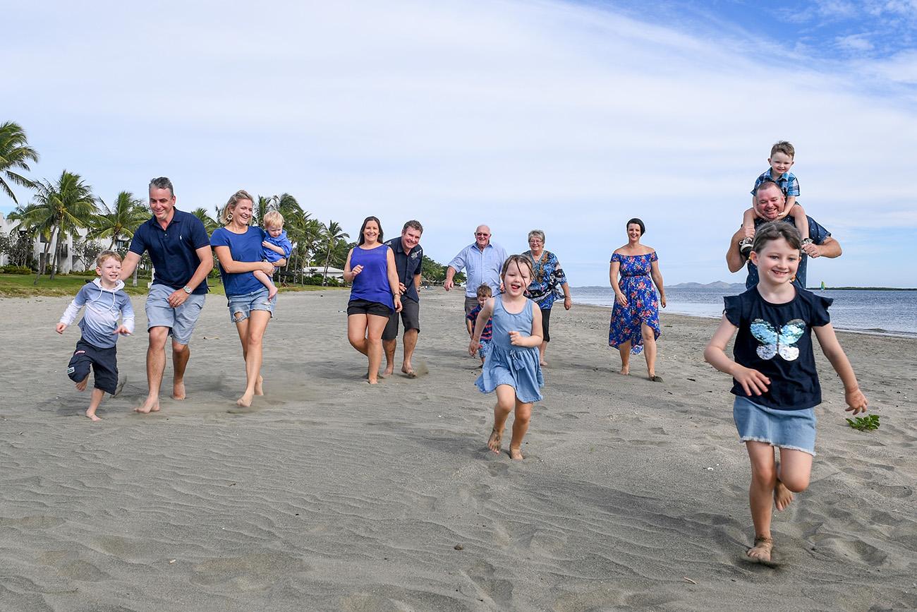 The extended family runs towards the camera while on Natadola beach