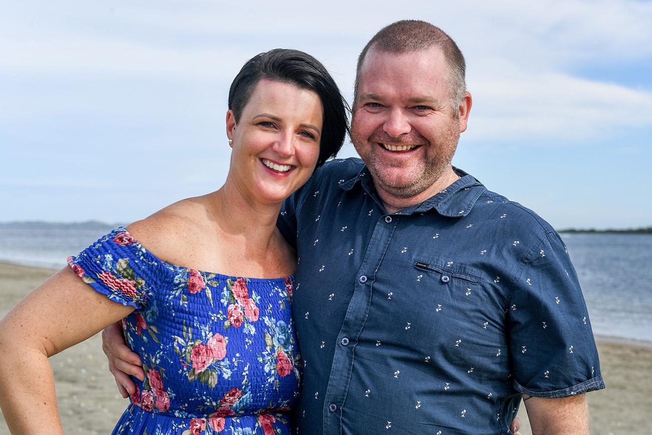 A loving couple in blue smile at the camera at Natadola Fiji