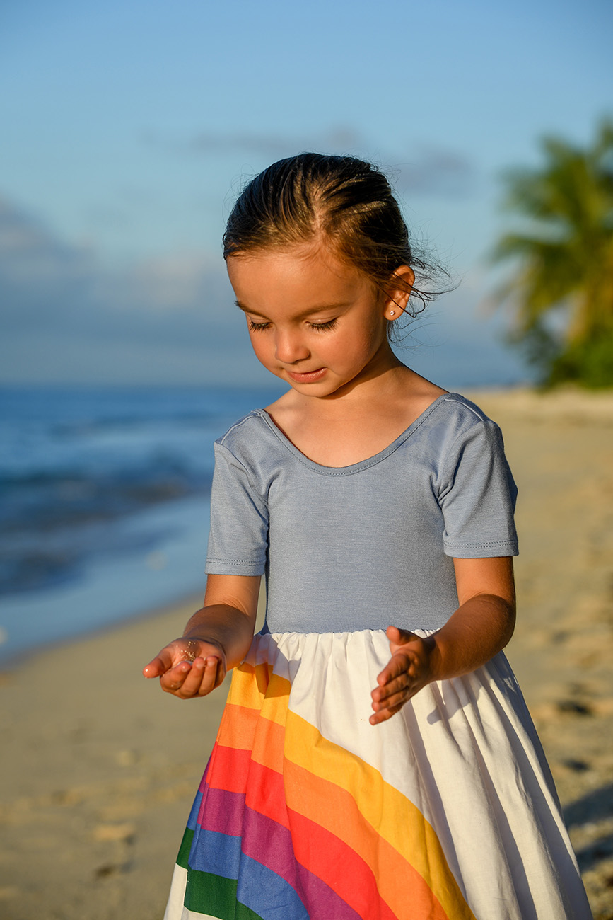 Cute girl in rainbow dresses plays with sand