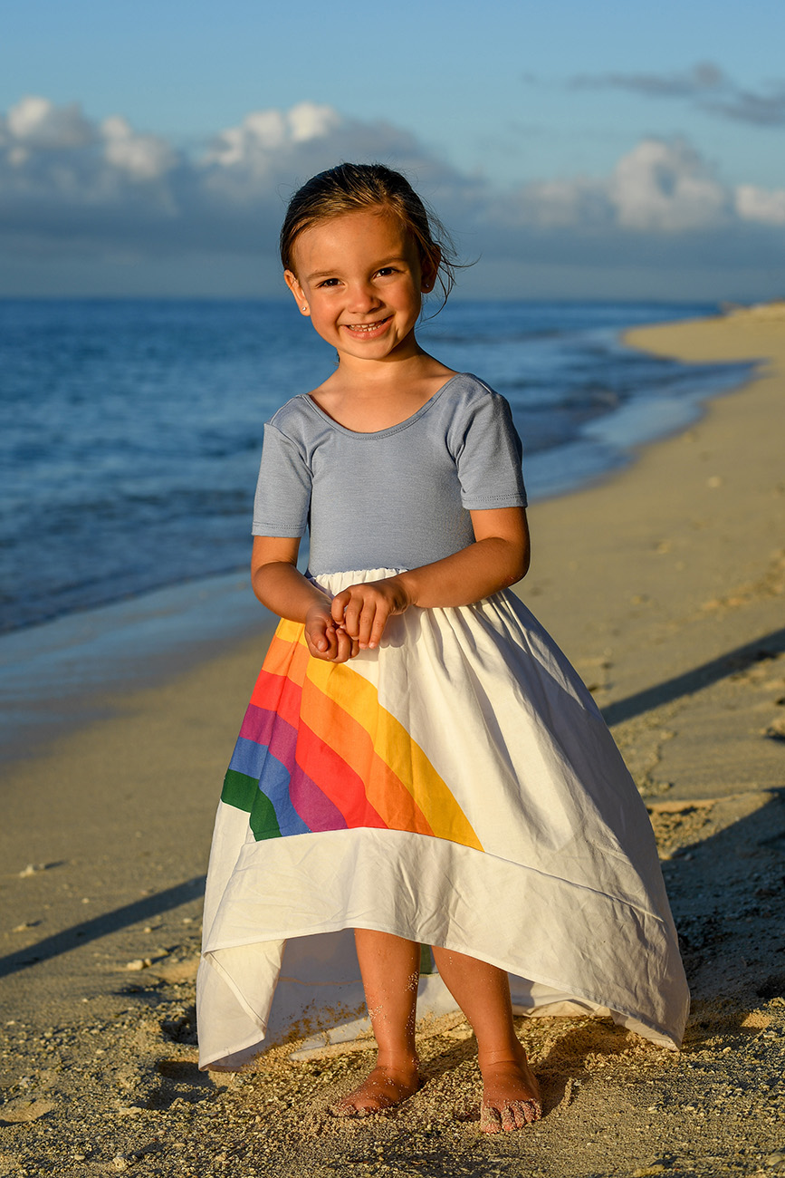 A full frame photo of a girl in a rainbow dress