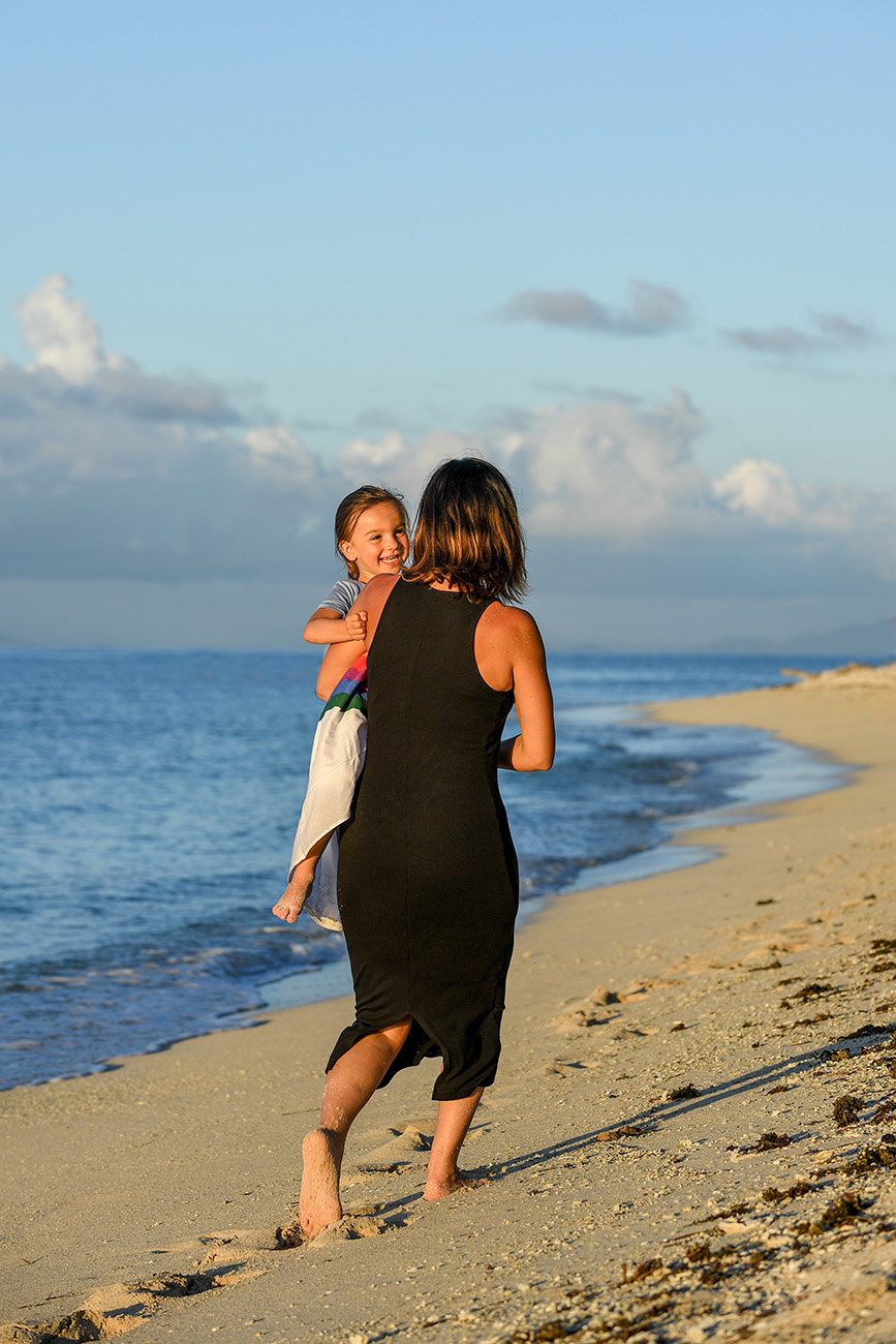 Mother and daughter play on the beach