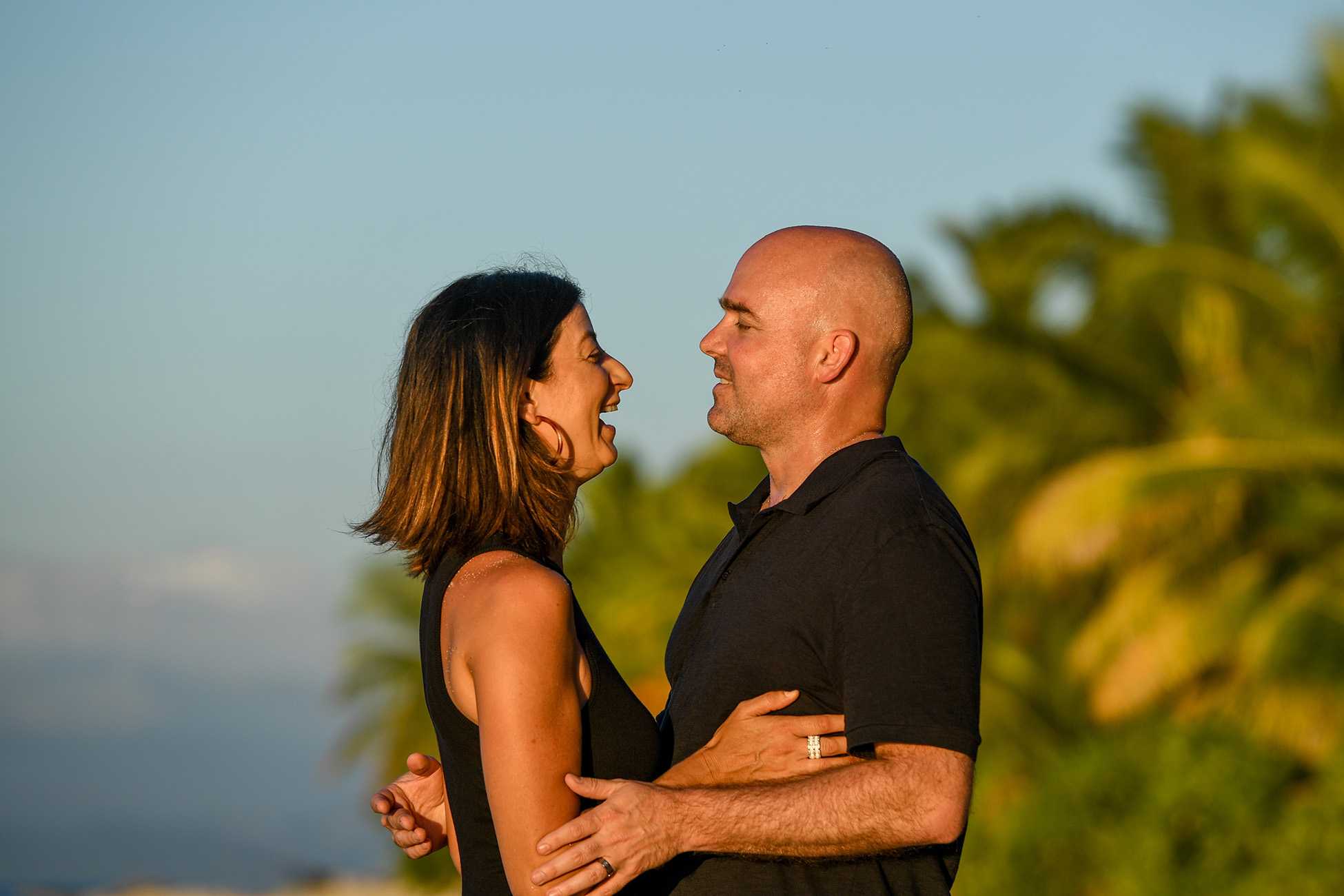 The lovely couple laughs in the sunset